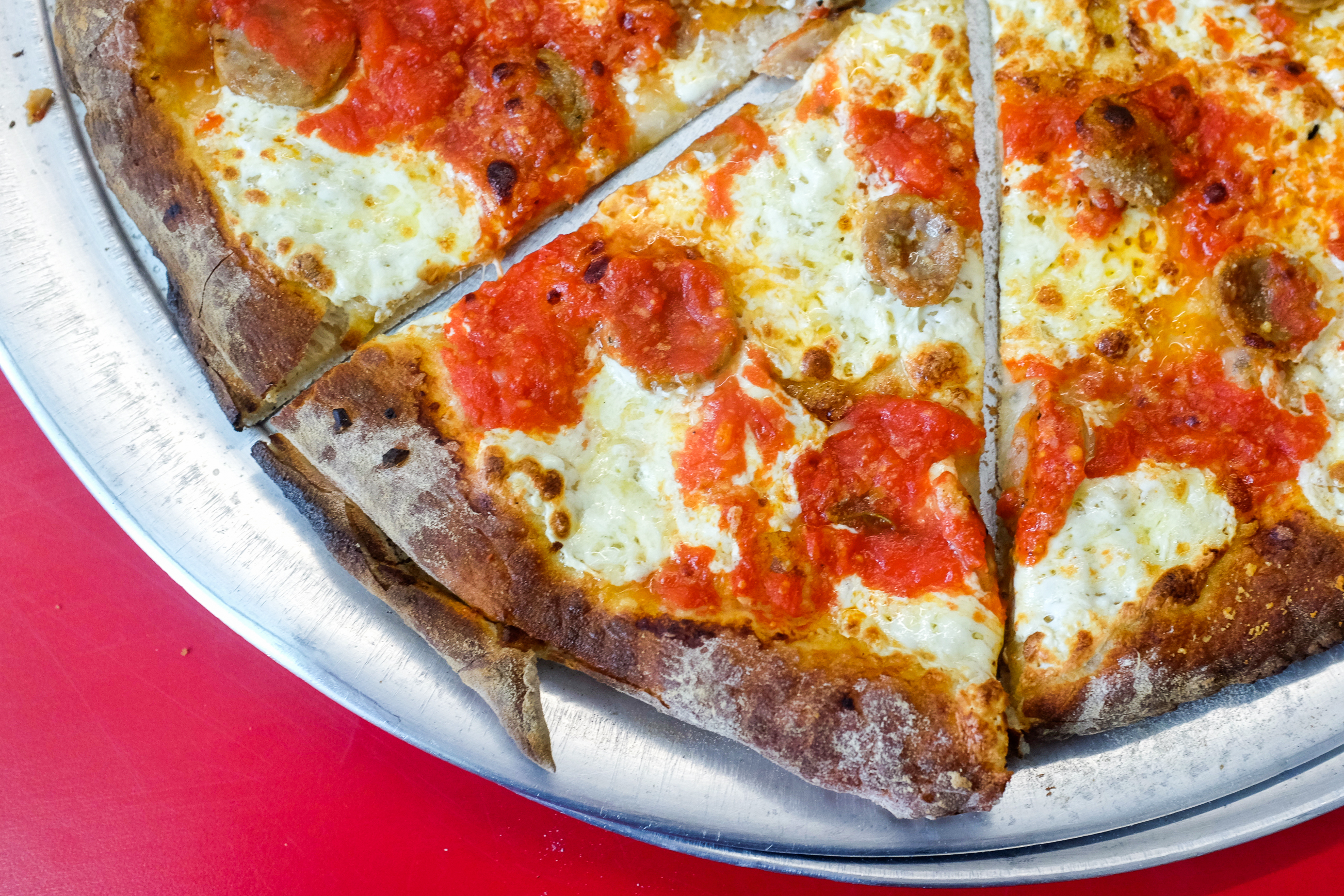 An overhead photograph of three slices of saucy pizza on a metal tray