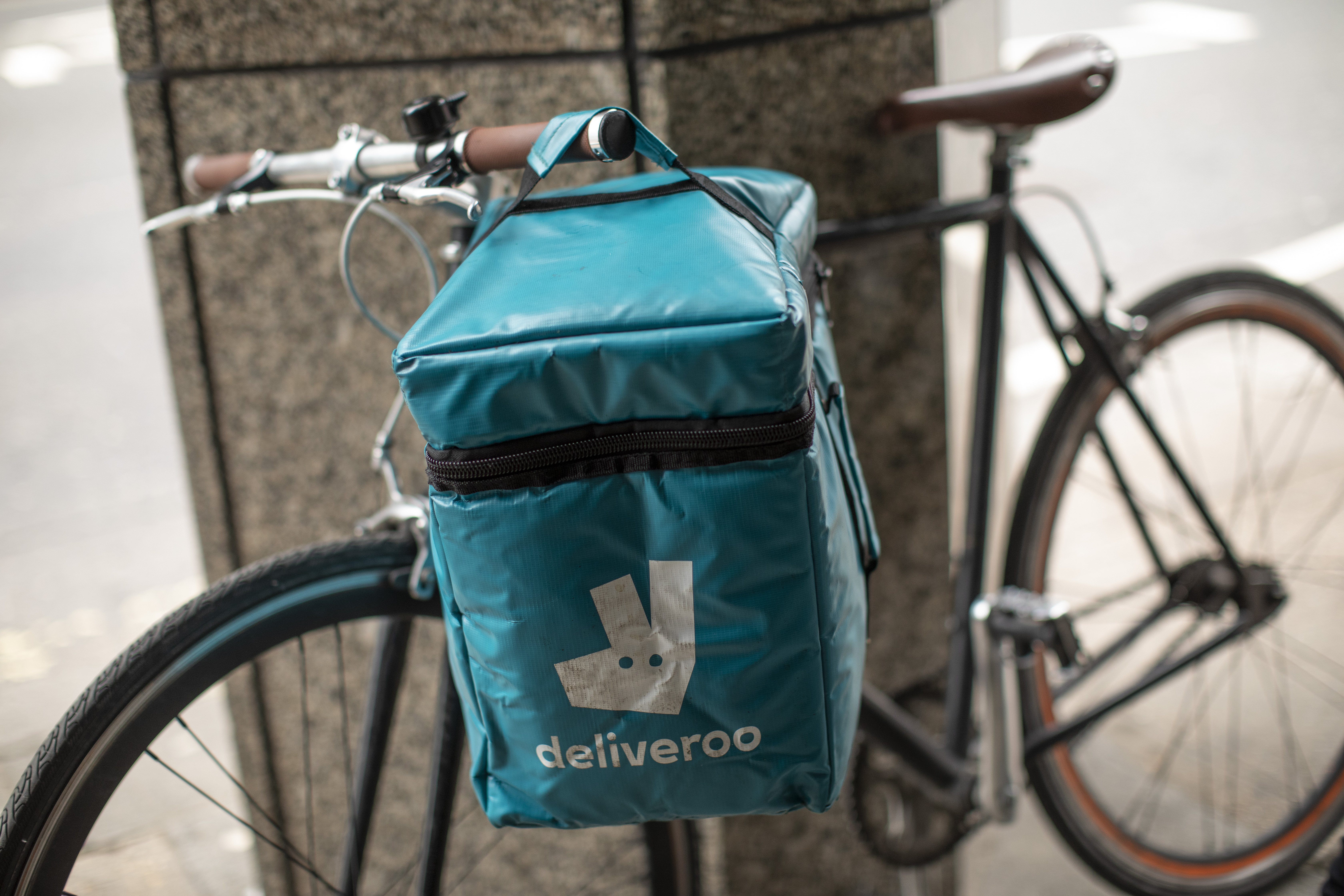 A Deliveroo bike with a blue delivery bag attached by a bin in central London
