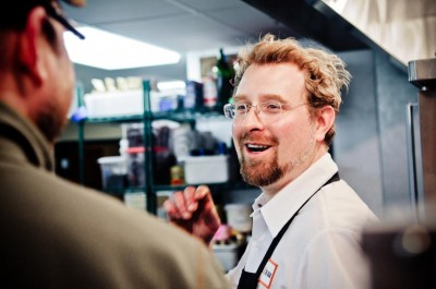 A blonde haired, bespectacled Peter Botcher laughing inside the kitchen at Butcher and the Boar