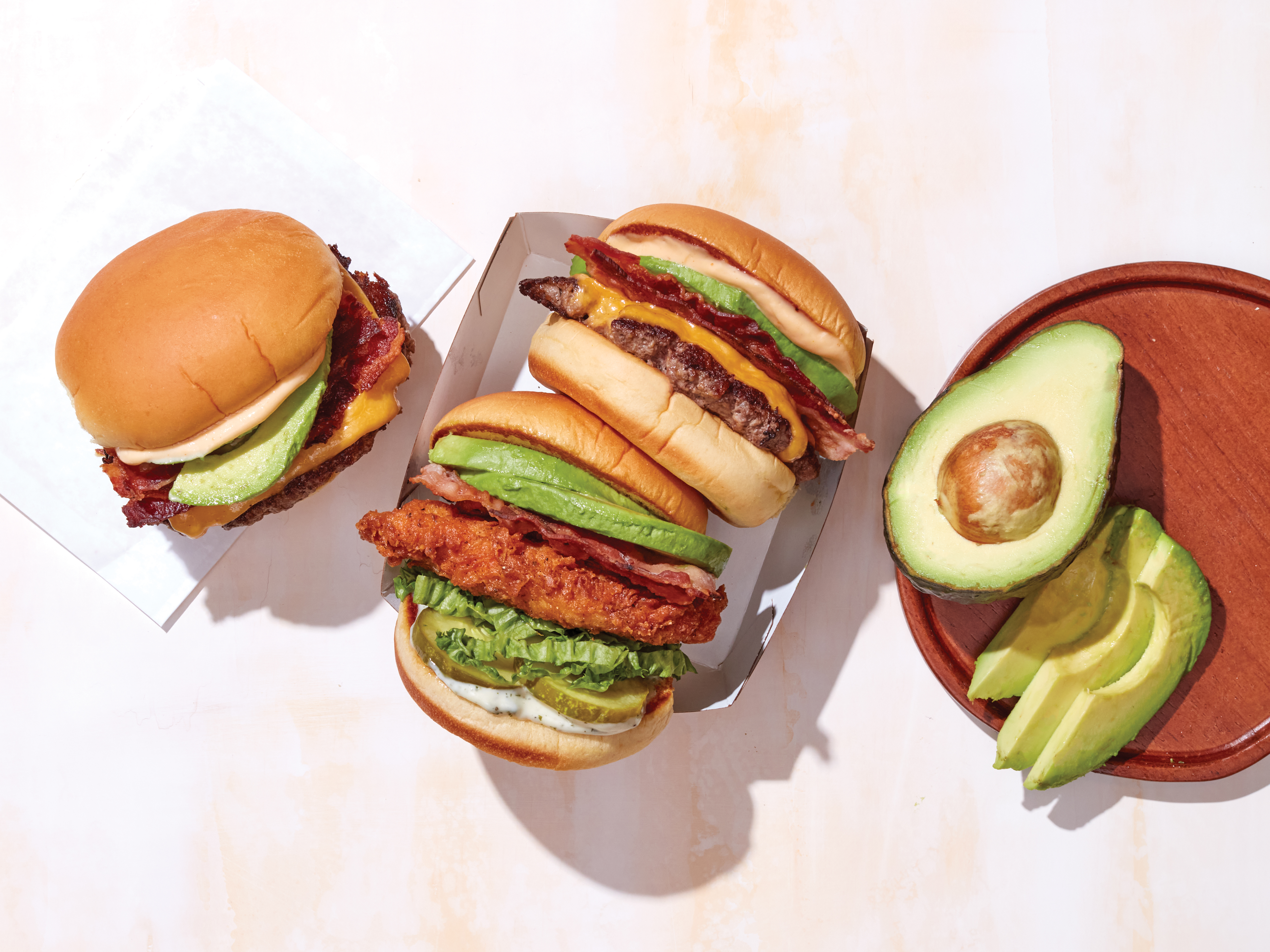 Burgers, chicken sandwiches, and a whole avocado sit on a table. These are Shake Shack's burgers and fried chicken sandwiches