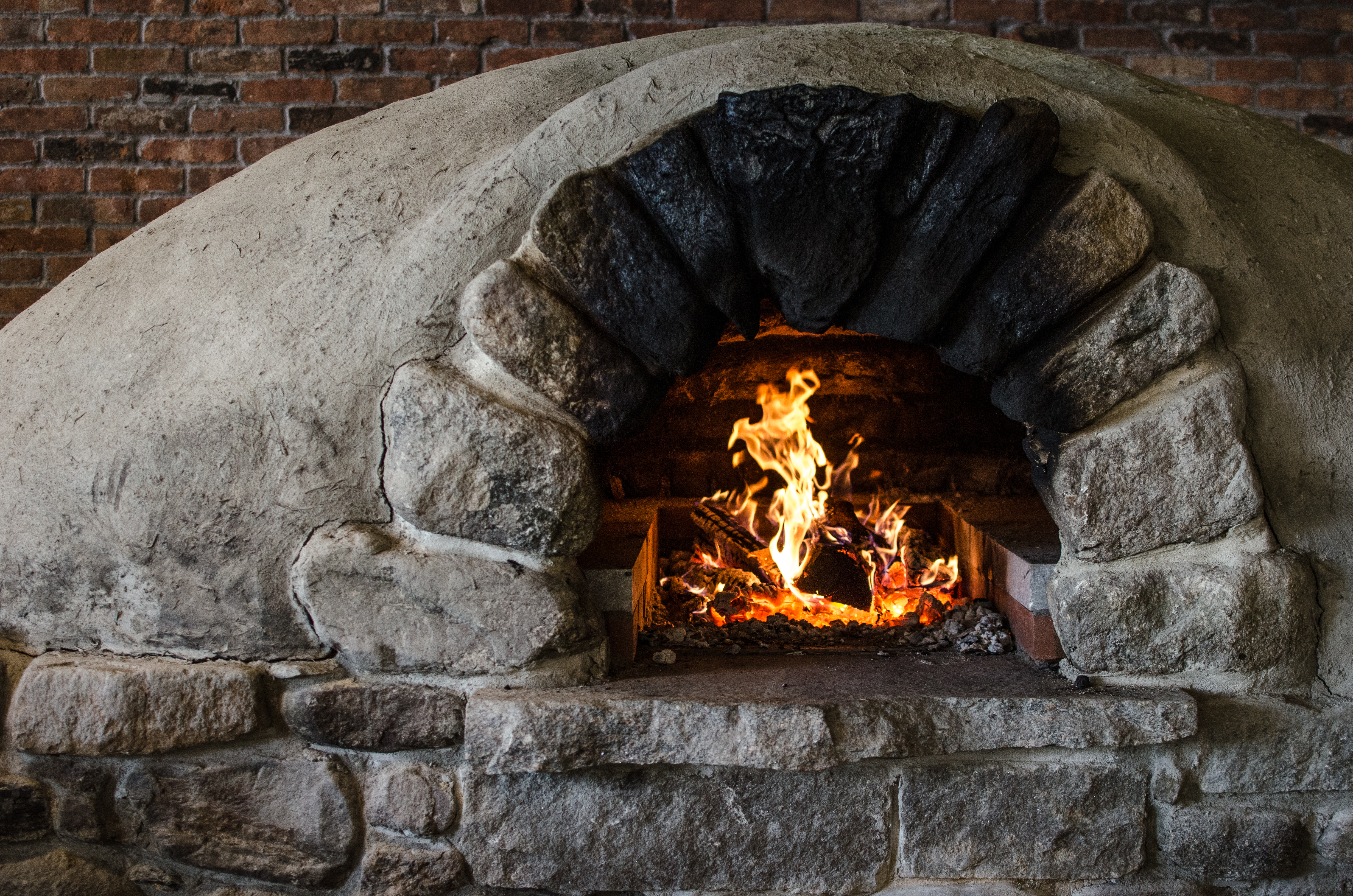 Closeup of a stone pizza oven with a fire going