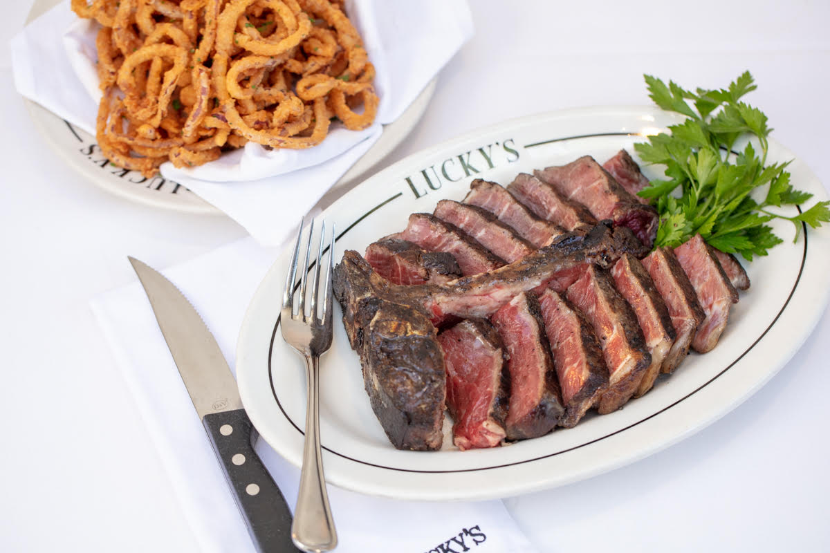 A white table shows a filet of steak next to a sharp knife.