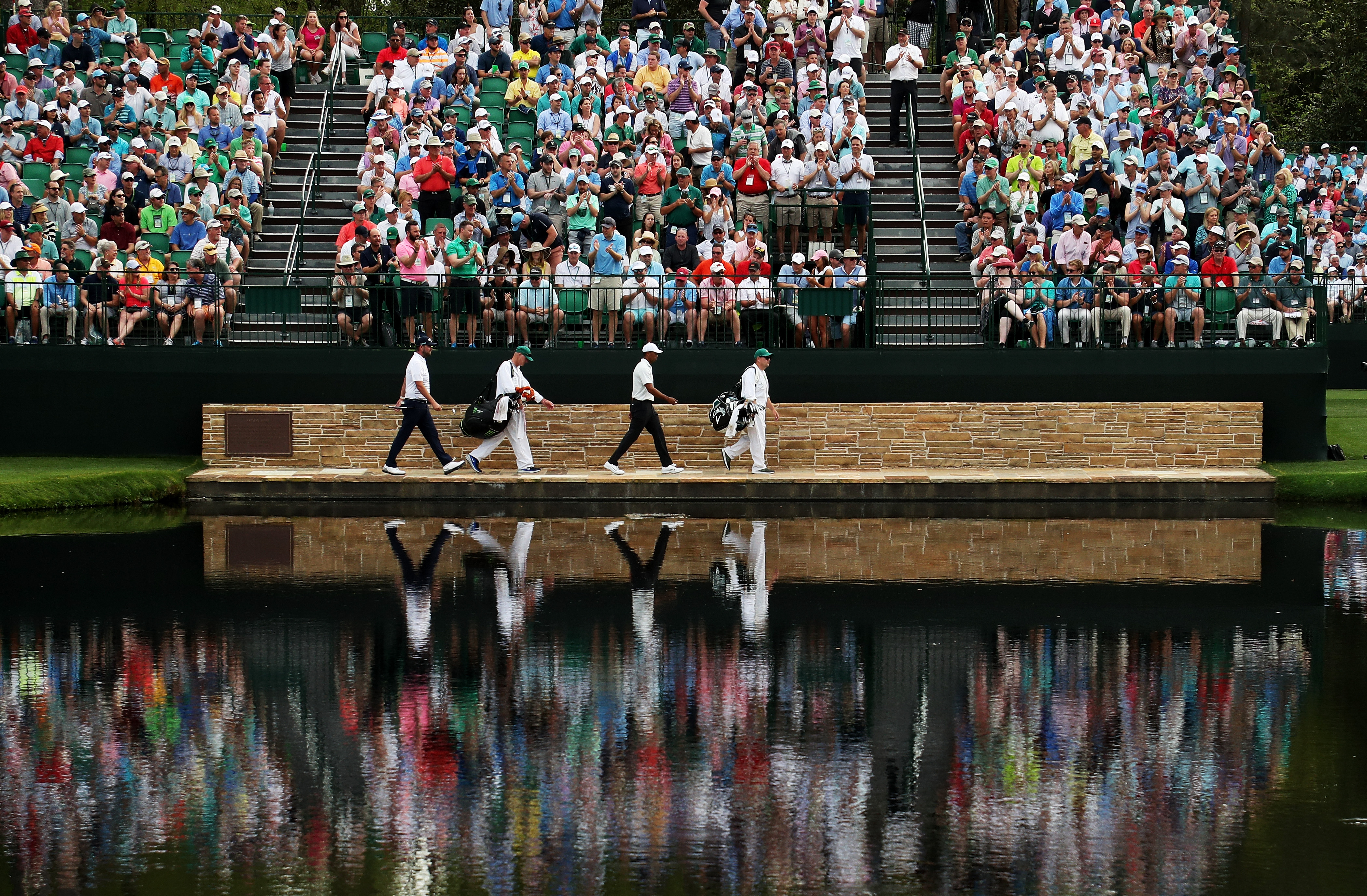Marc Leishman of Australia and Tiger Woods of the United States cross the Sarazen Bridge on the 16th hole during the second round of the 2018 Masters Tournament at Augusta National Golf Club on April 6, 2018 in Augusta, Georgia.