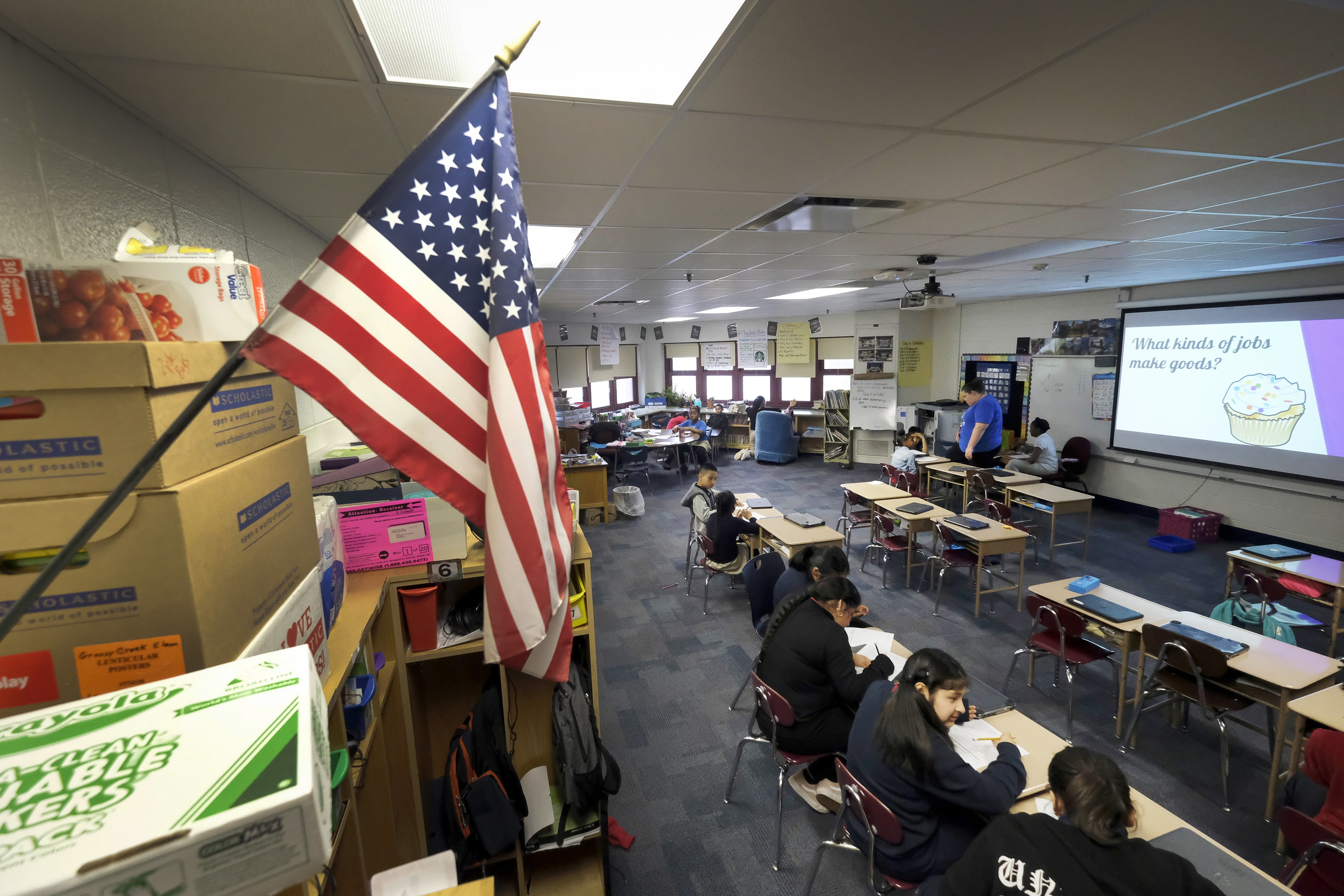 An American flag hangs on a wall in April 2019, in an elementary  classroom with a few students sitting in a row