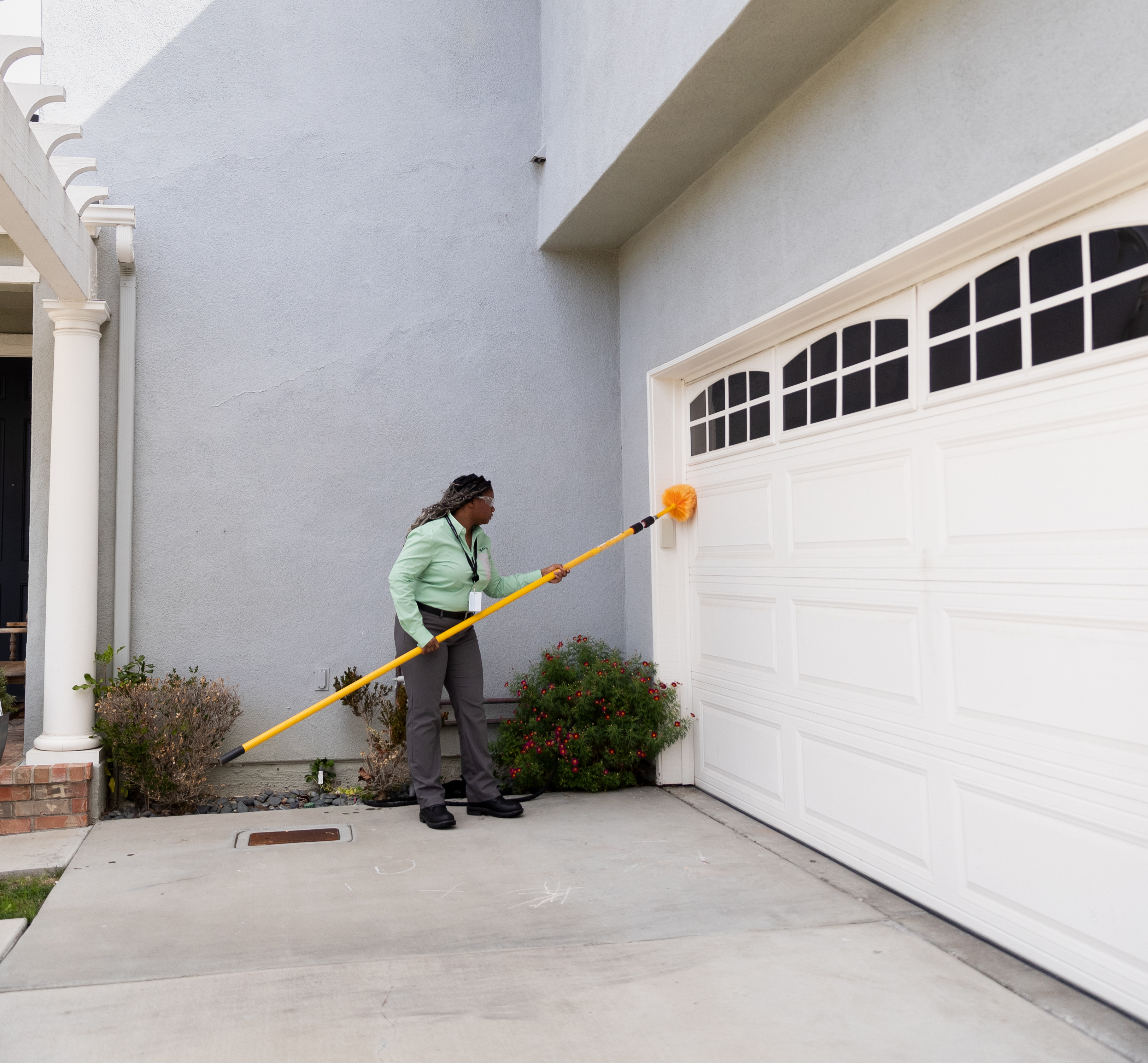 A pest control specialist wearing a green shirt and grey pants uses a yellow pest control wand to clean a white garage door on the exterior of a grey house.