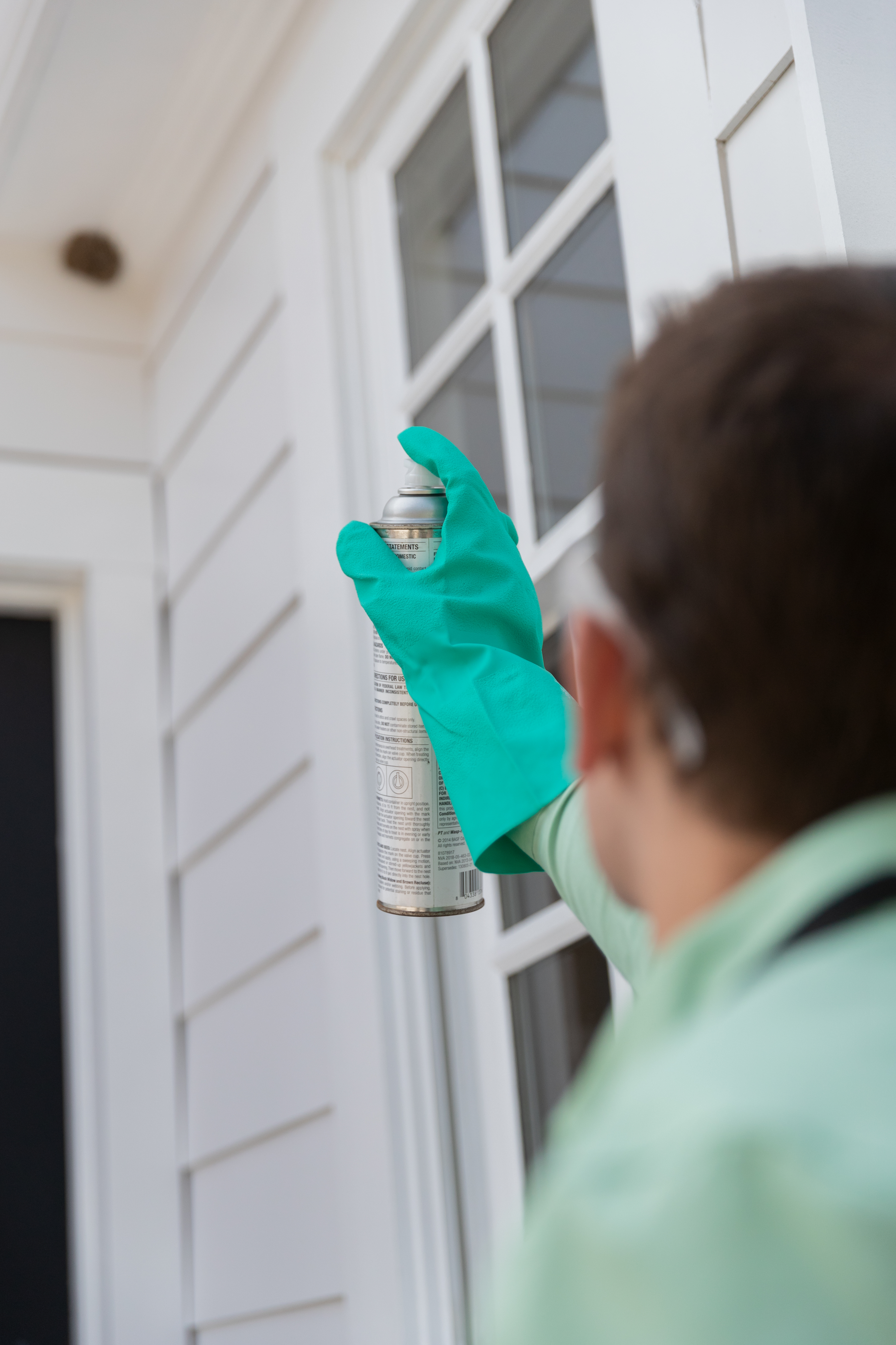 A pest control specialist wearing a green shirt and green gloves sprays pest control solution in the direction of an insect nest on a white house.