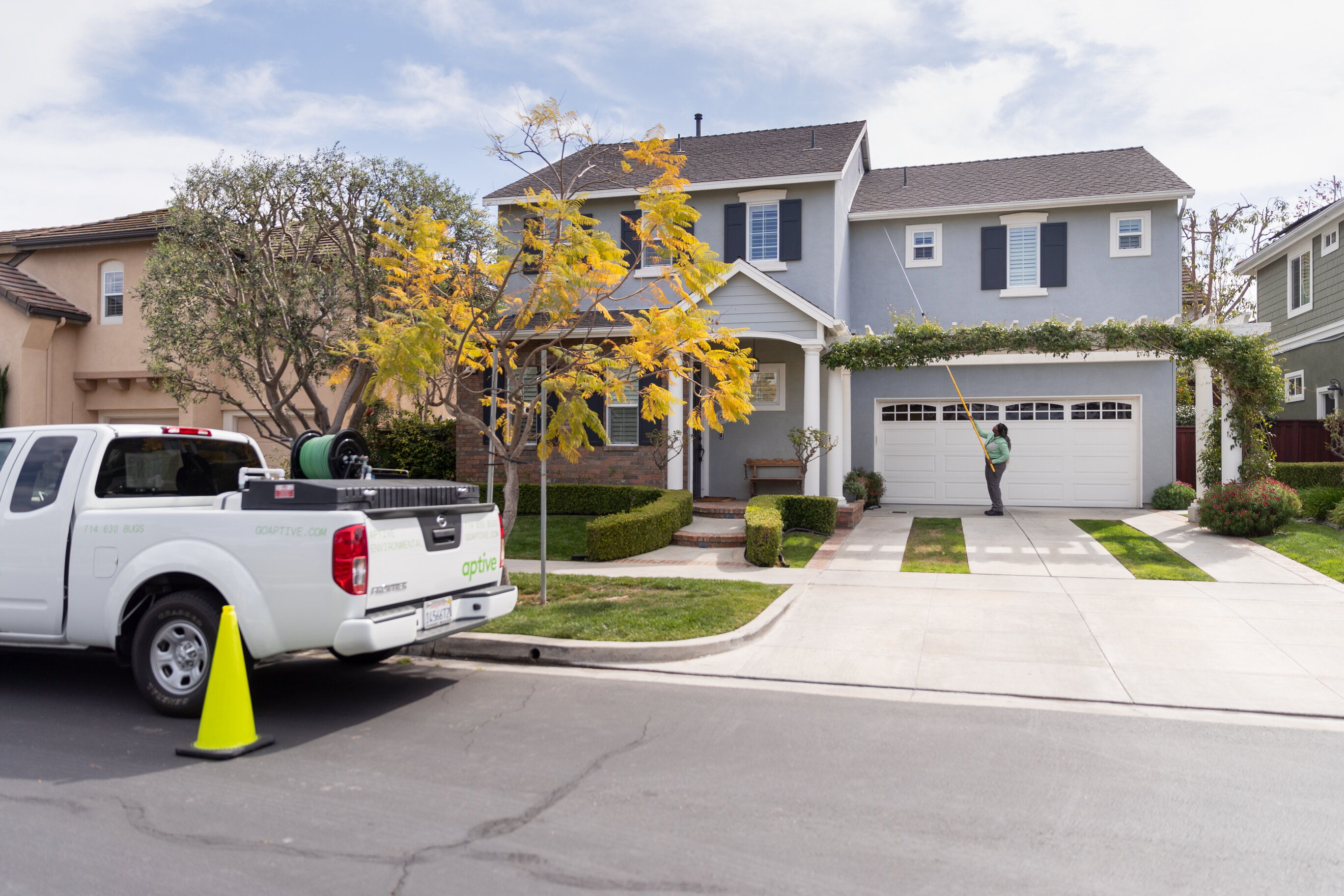 A pest control specialist wearing a green shirt and grey pants uses a yellow pest control wand on the exterior of a white garage door on a grey house. Seen on the street is a white Aptive pick-up truck with other pest control tools in the bed.