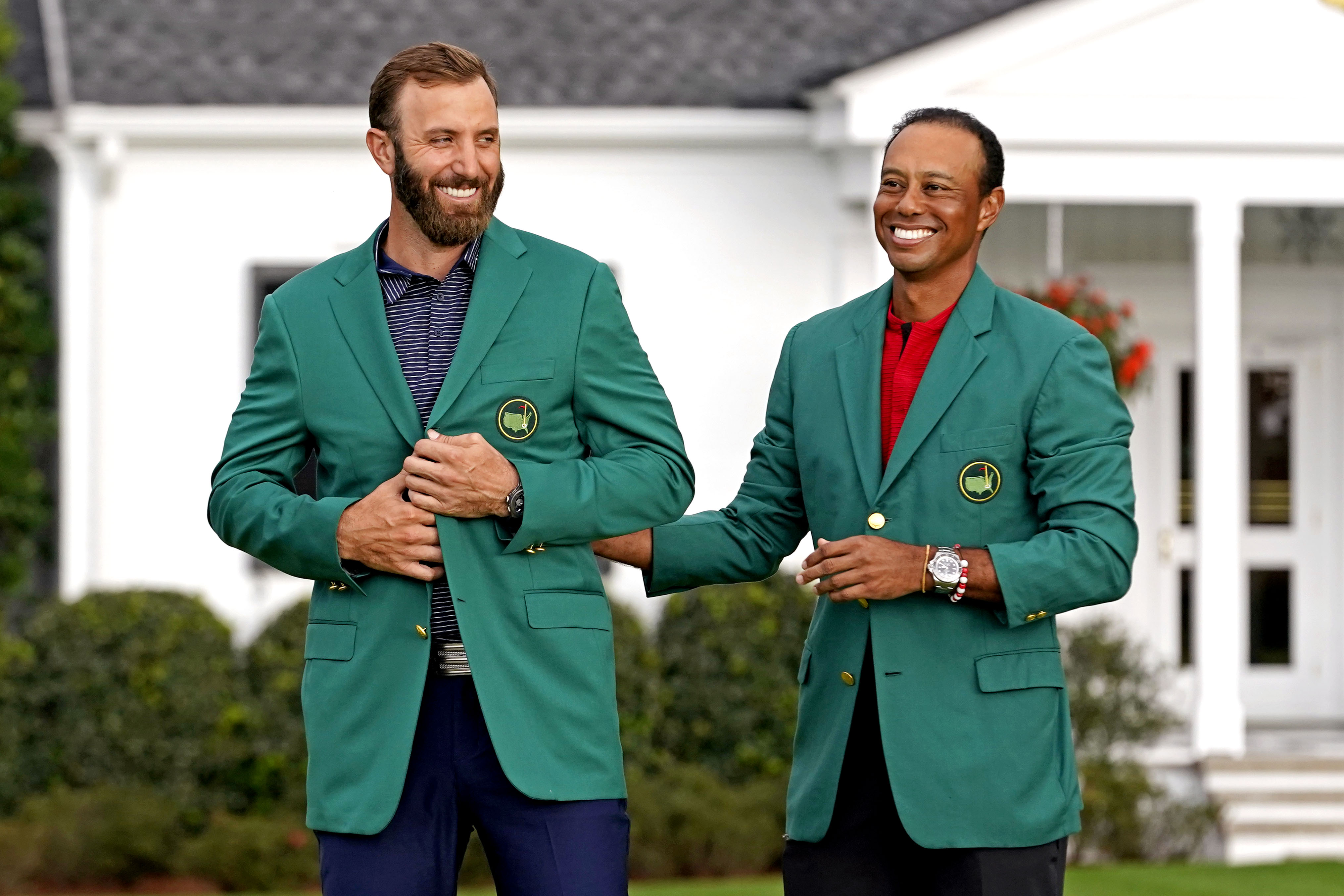 2019 Masters champion Tiger Woods presents Dustin Johnson with the green jacket after winning The Masters golf tournament at Augusta National GC.