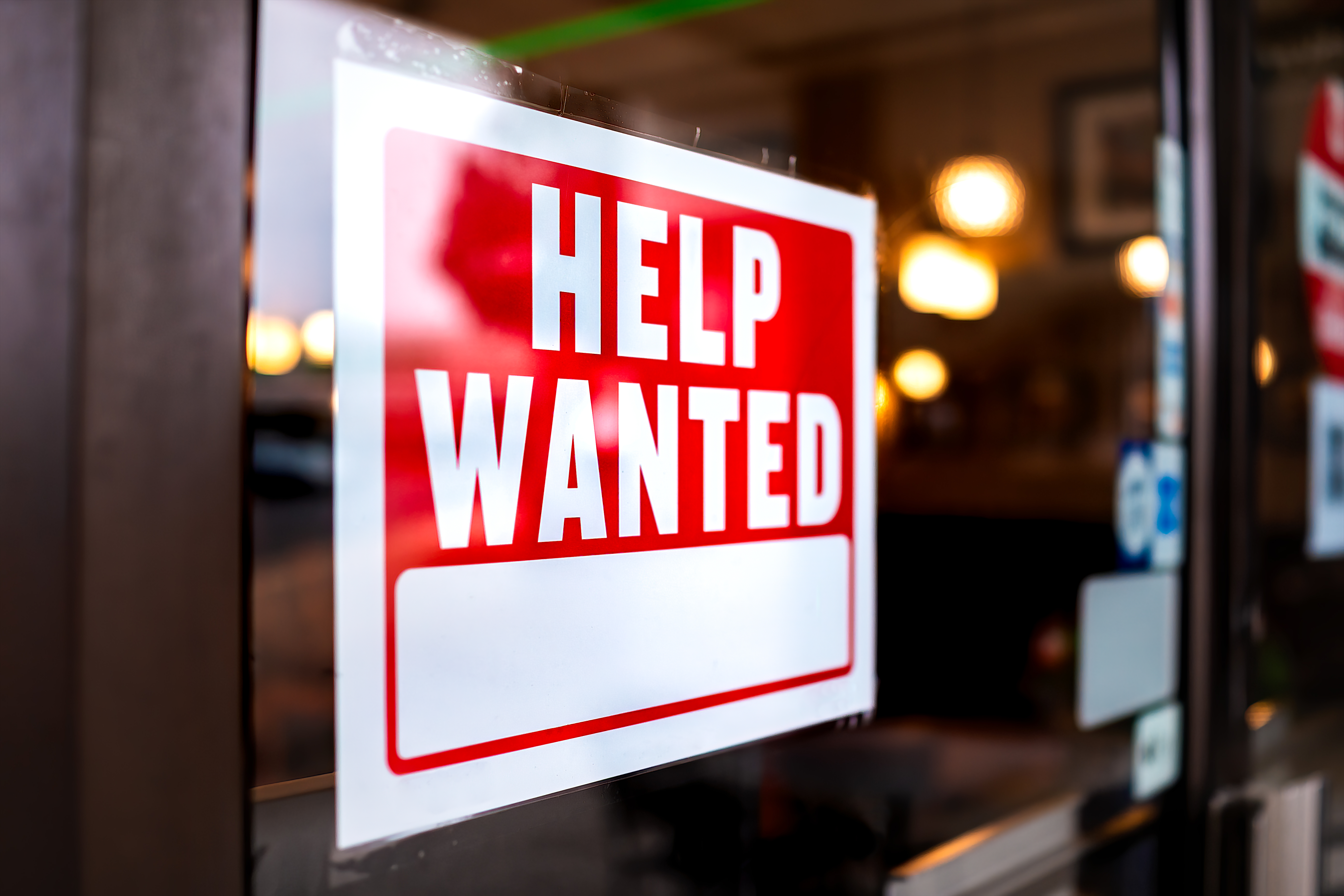 A red and white help wanted sign hangs in the window