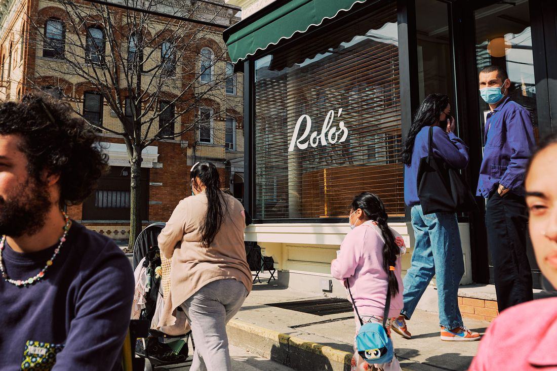 """People walk on the sidewalk past a restaurant window with the logo """"Rolo's"""" emblazoned on the window pane"""