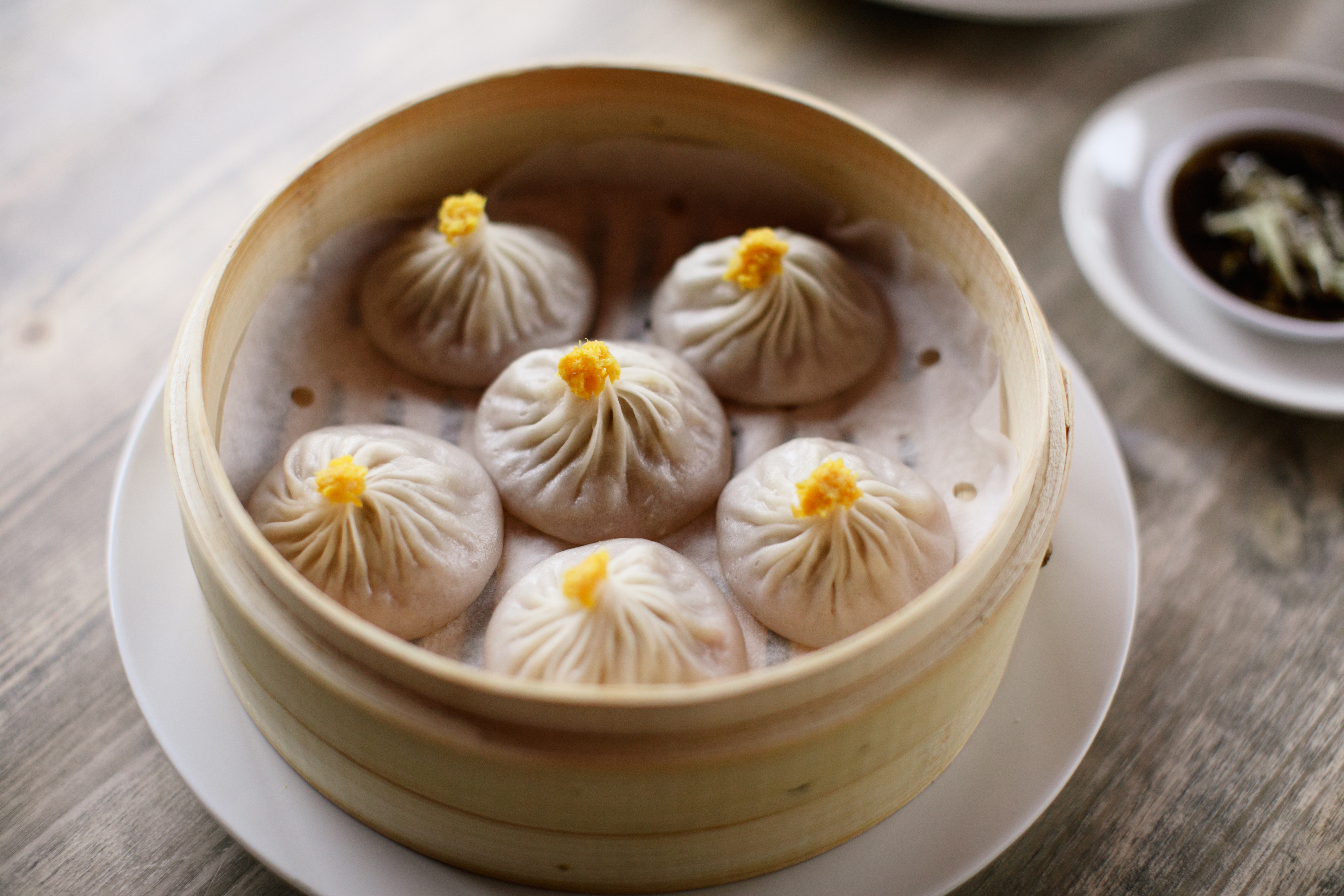 basket with six soup dumplings with yellow tips