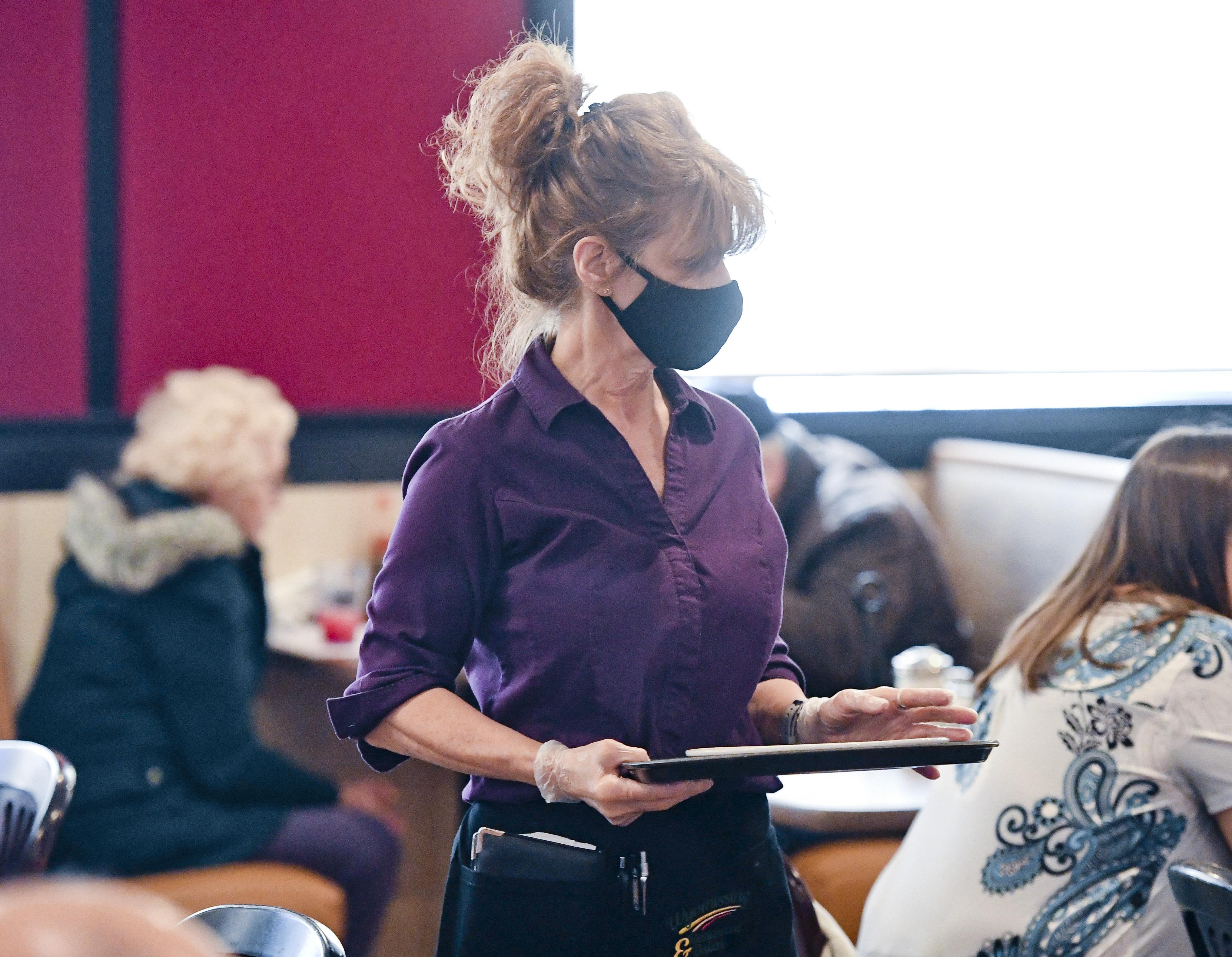 Restaurant server wearing a mask taking orders inside.