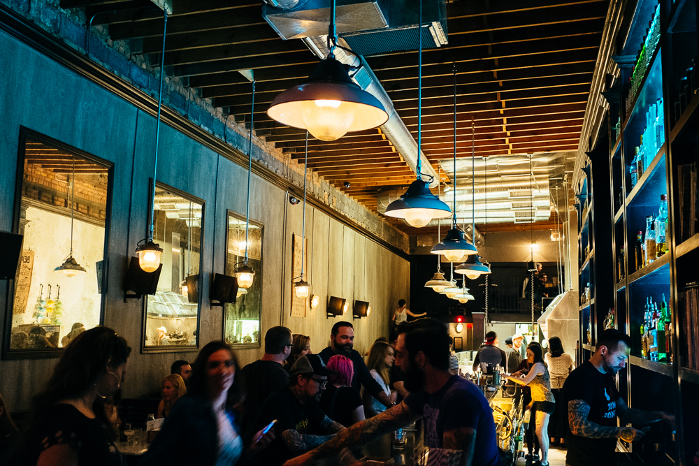 People gather at the bar inside Public House. The room is dark, narrow, and crowded.