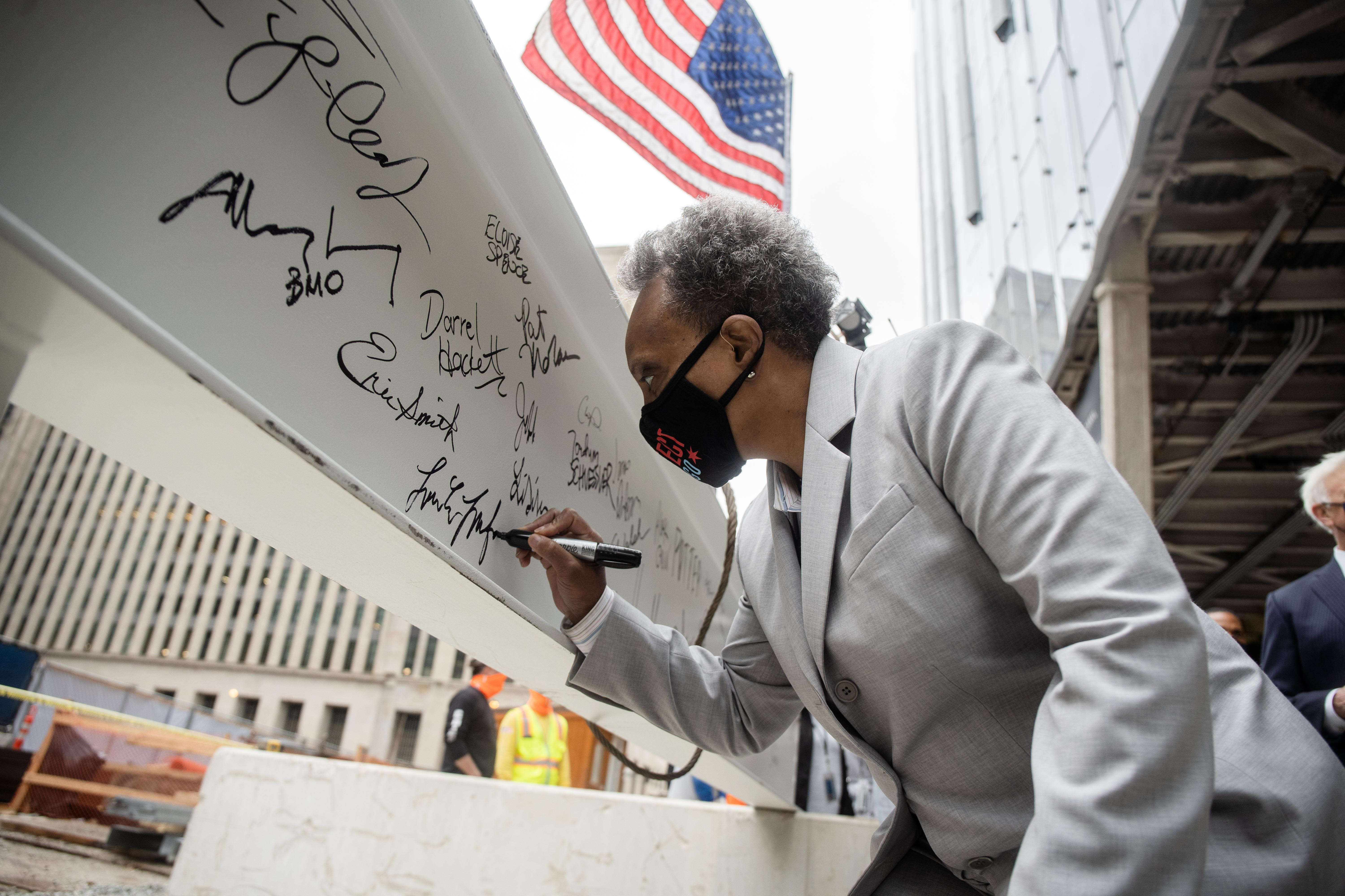 Chicago Mayor Lori Lightfoot signs a beam during the topping off ceremony at BMO Tower, located at 320 S. Canal St. in the West Loop Gate, Thursday morning, April 8, 2021.