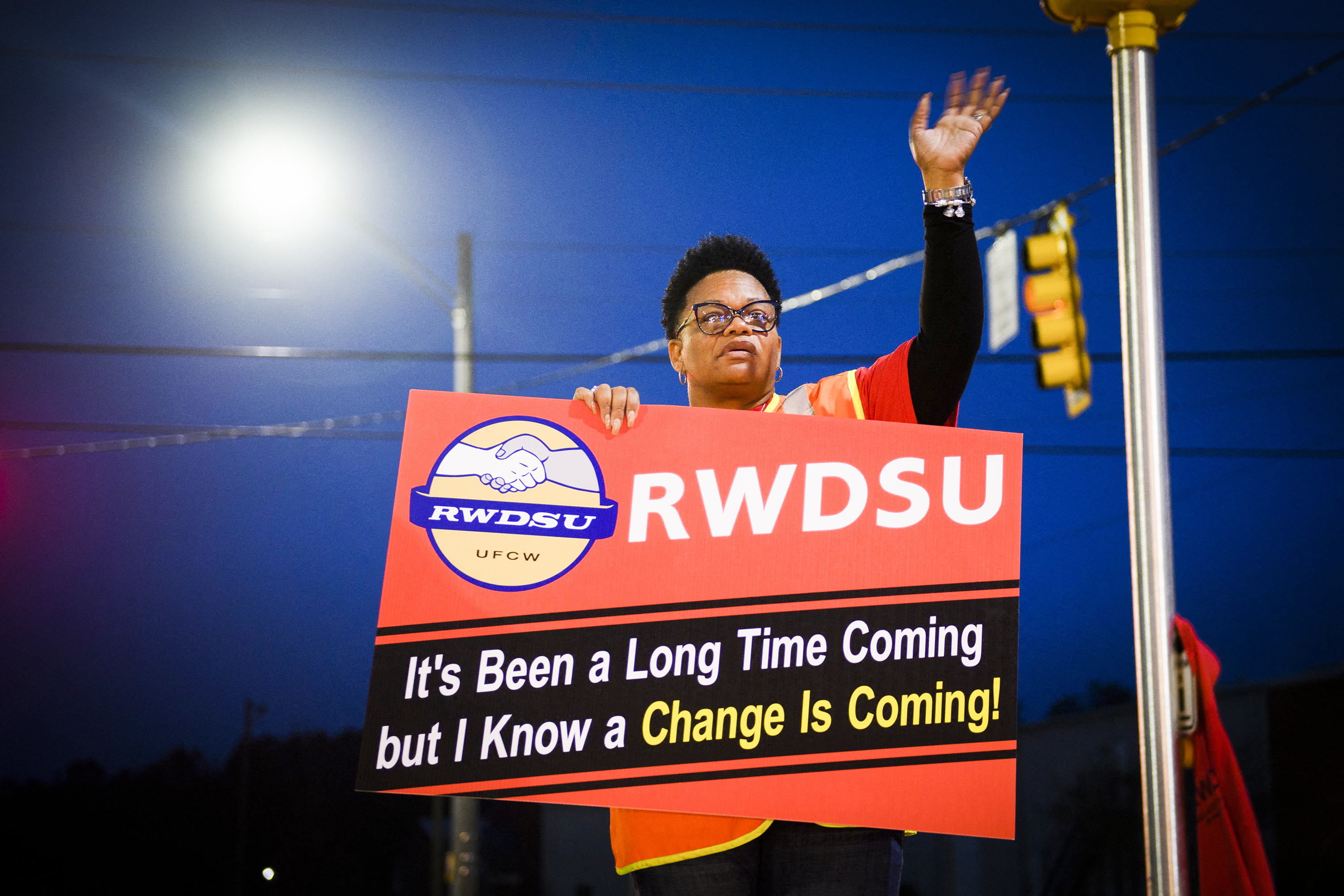 "A union organizer holds a sign that reads, ""RWDSU. It's been a long time coming but I know a change is coming!"""