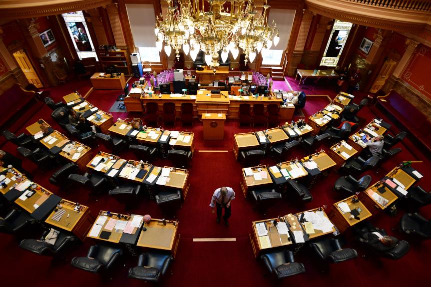 A lone senator walks down the center aisle of the Colorado State Senate. Desks are arrayed in a semi-circle facing an elaborate dais.