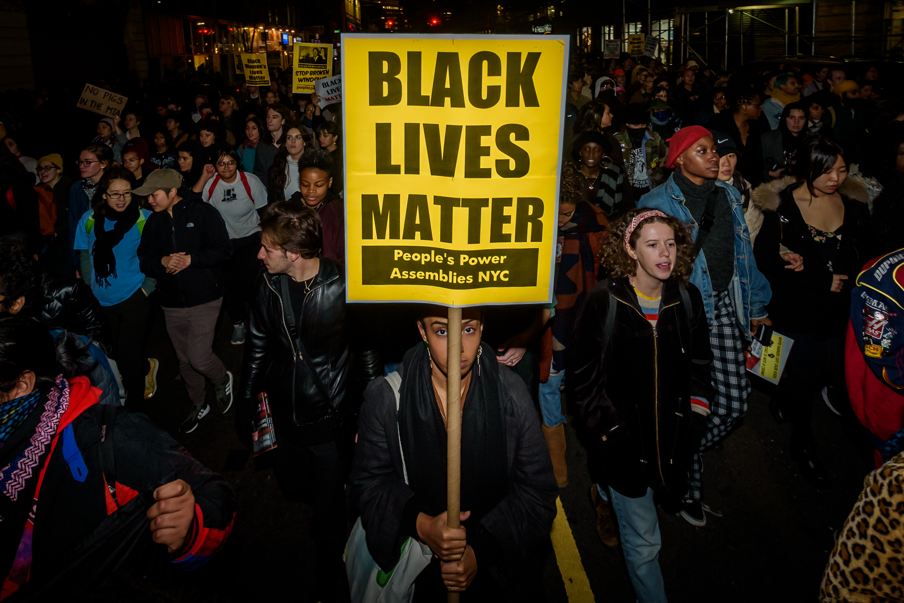 "A protester in a crowd holds a sign that reads, ""Black Lives Matter."""