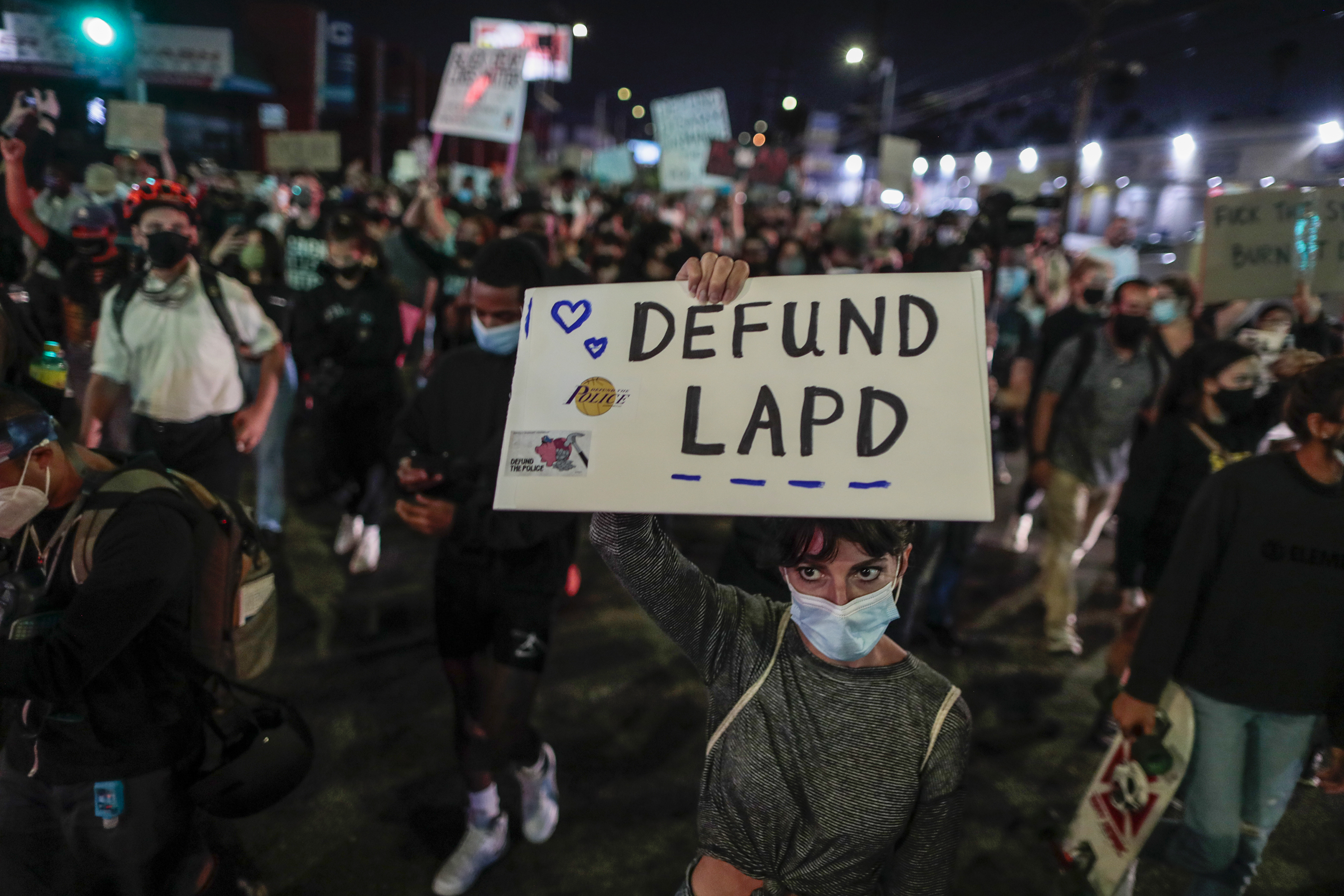 "A protester in a large group of protesters holds a sign that reads, ""Defund LAPD."""
