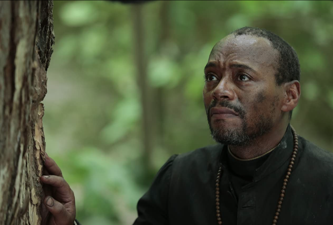A Black man in a priest's robe stands in a forest.