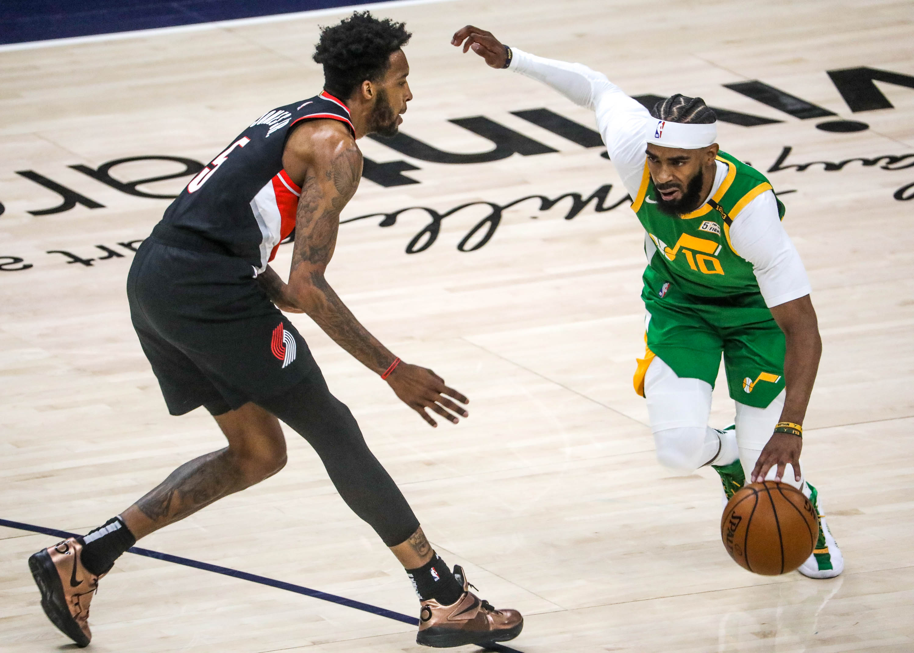 Utah Jazz guard Mike Conley (10) moves past Portland Trail Blazer forward Derrick Jones Jr. (5) during the game at Vivint Smart Home Arena in Salt Lake City on Thursday, April 8, 2021.