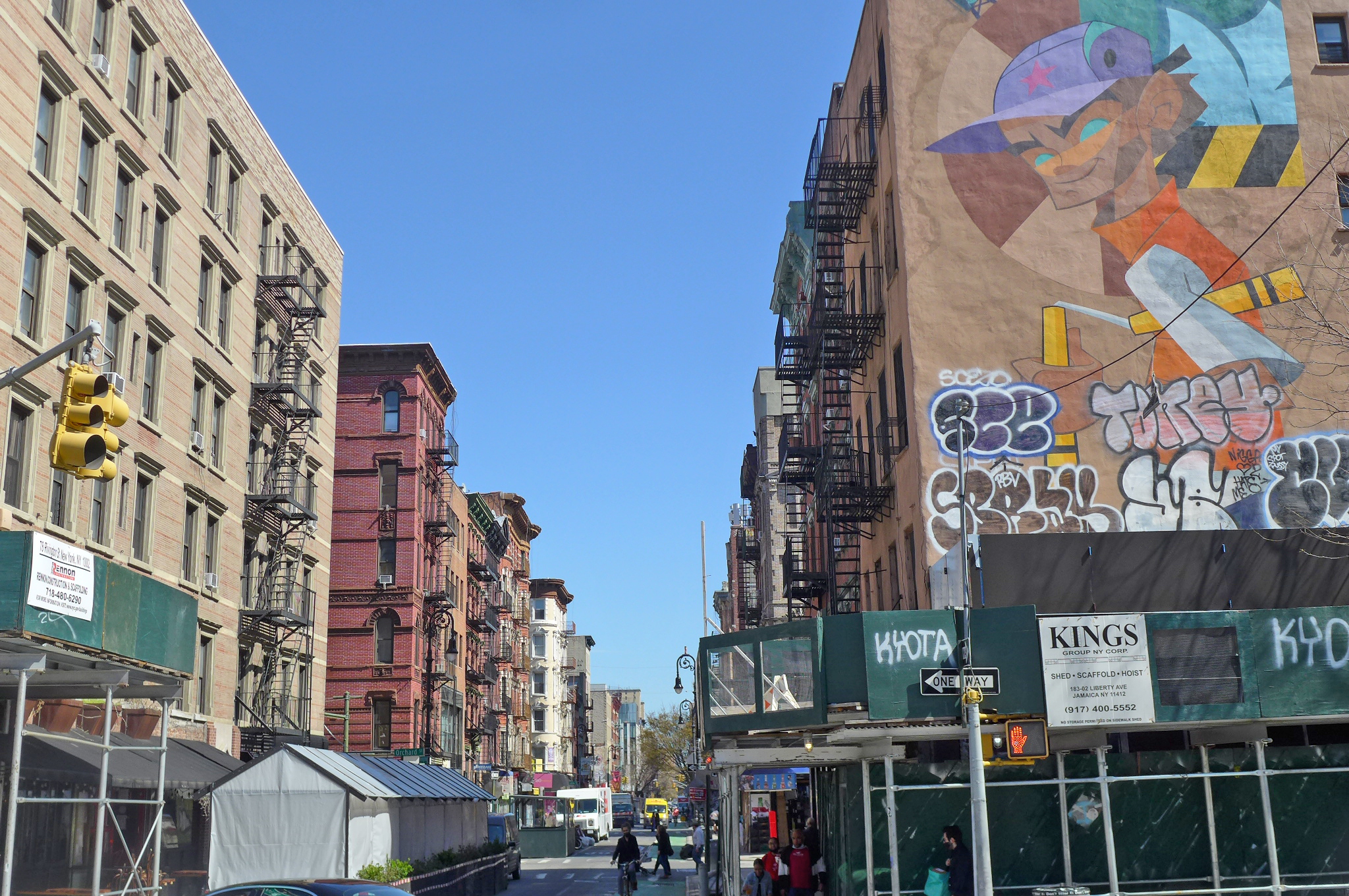 Two rows of receding tenements with a sliver of blue sky in between.