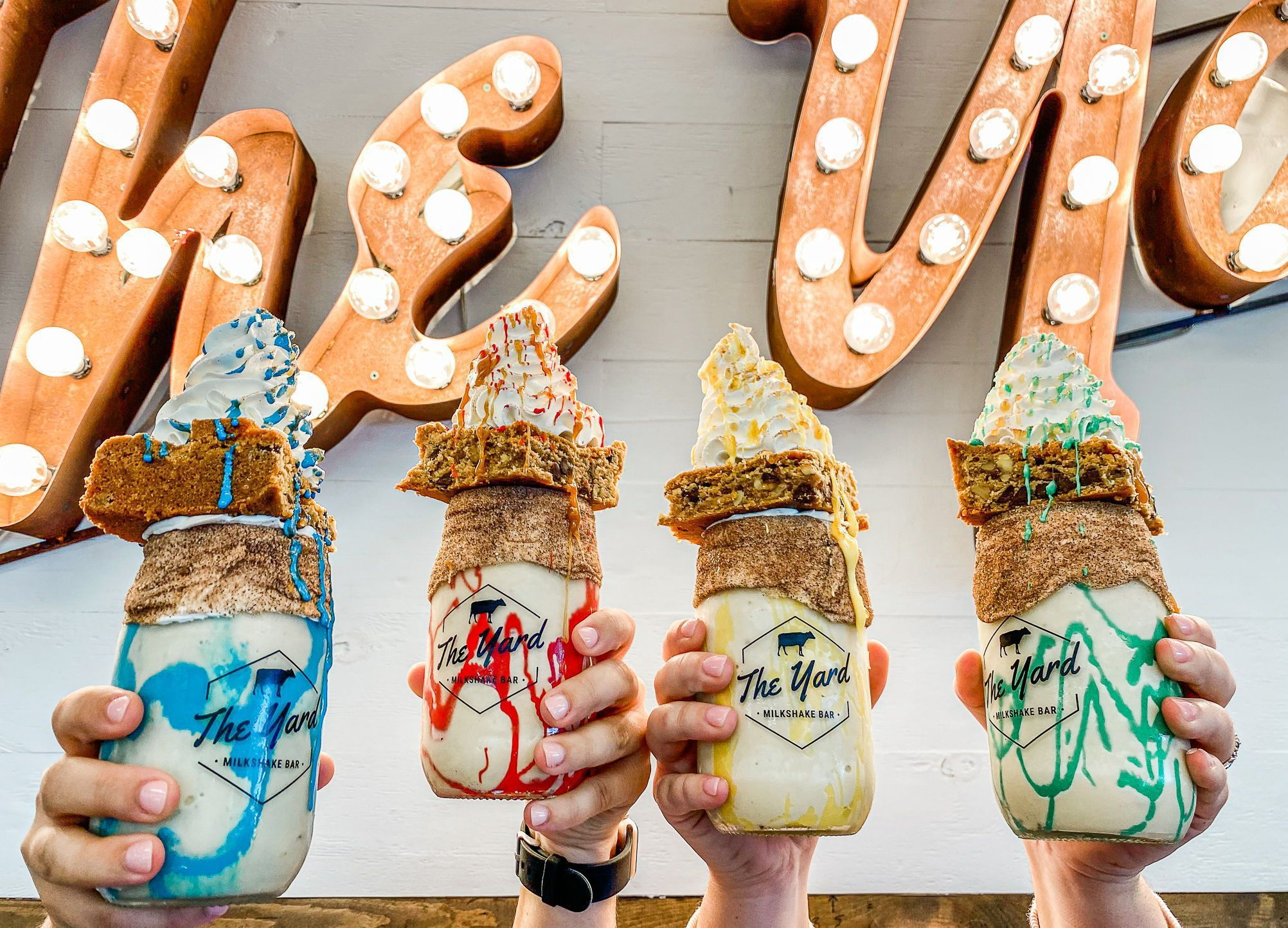 Four hands hold up mason jars filled with milkshakes swirled with colors like yellow, green, red, and blue, topped with blondies and swirls of whipped cream.