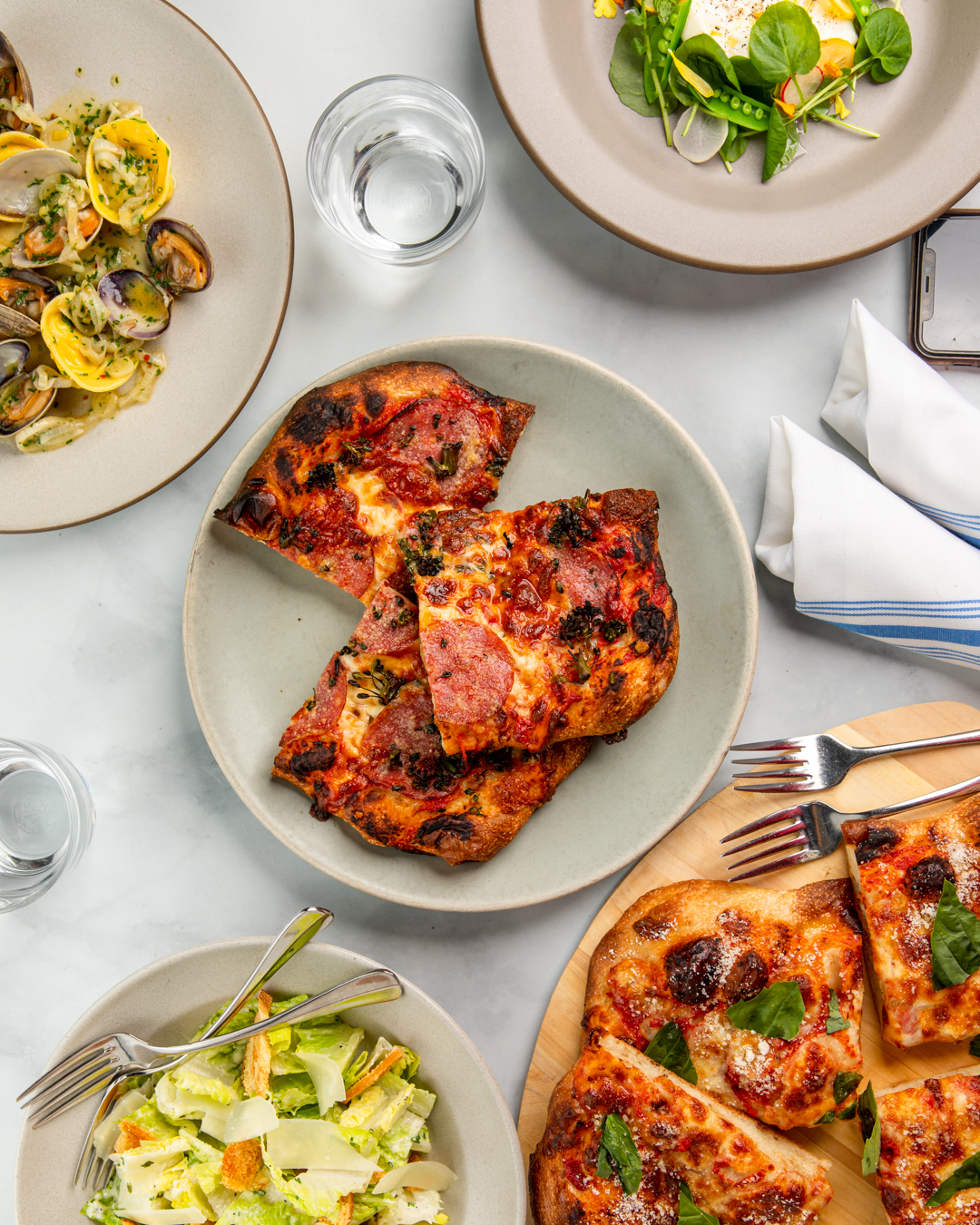 An overhead photograph of several plates filled with Italian dishes, including slices of pizza, pasta, and clams