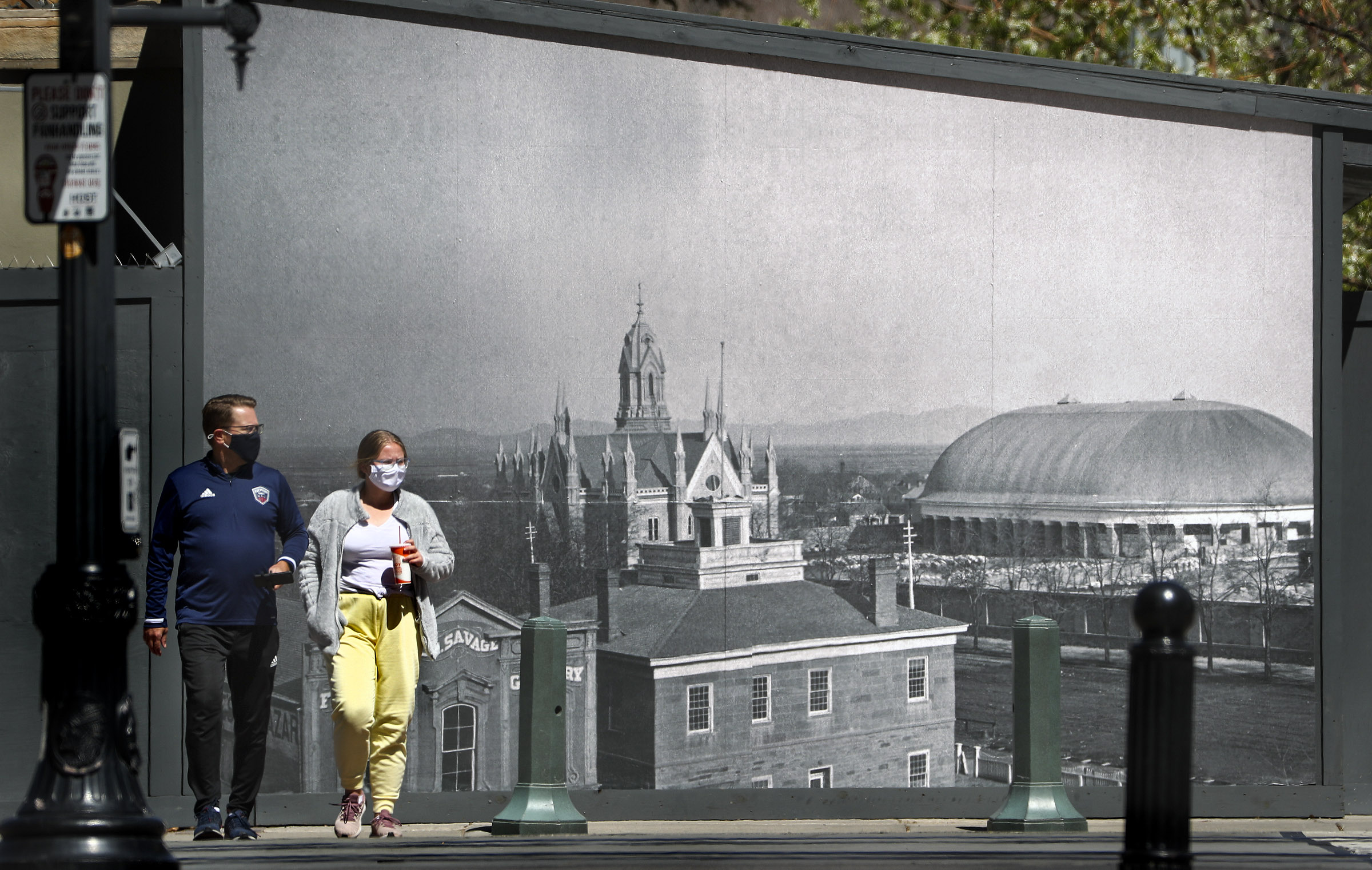 Pedestrians wearing masks cross South Temple as they walk along Main Street in front of a historical mural of Temple Square in downtown Salt Lake City on Friday, April 9, 2021.