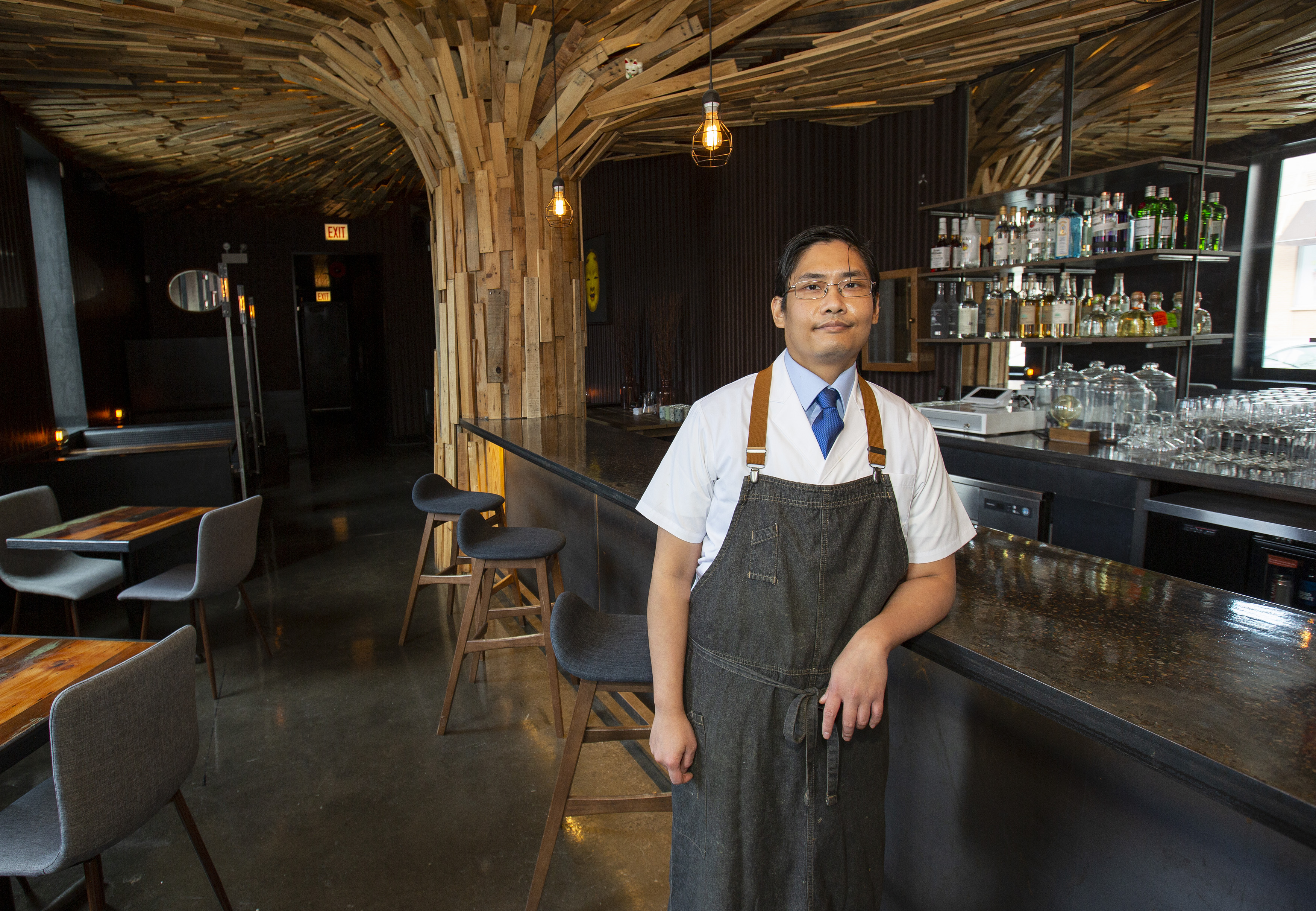 A chef wearing a dark apron leaning against a bar.