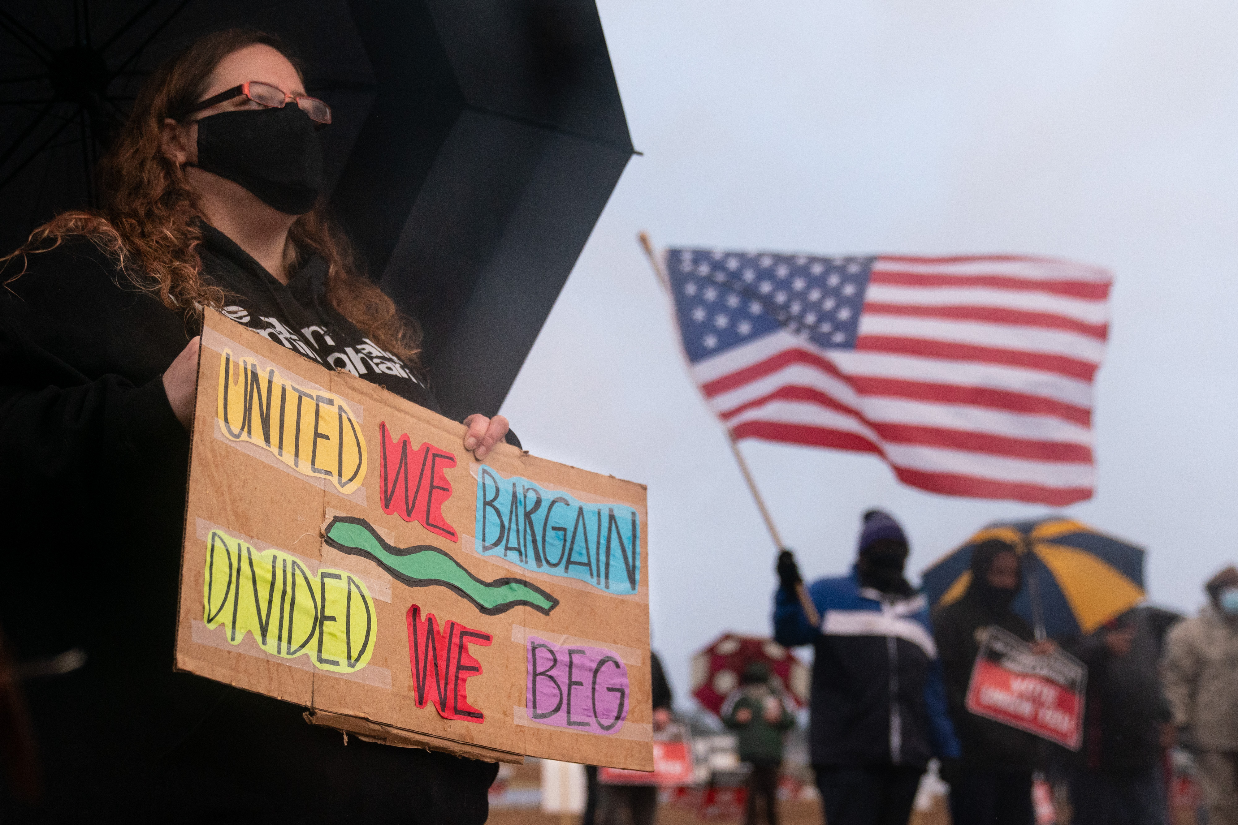 "A protester holds a sign near Amazon's Bessemer, Alabama, warehouse that reads, ""United we bargain, divided we beg."""