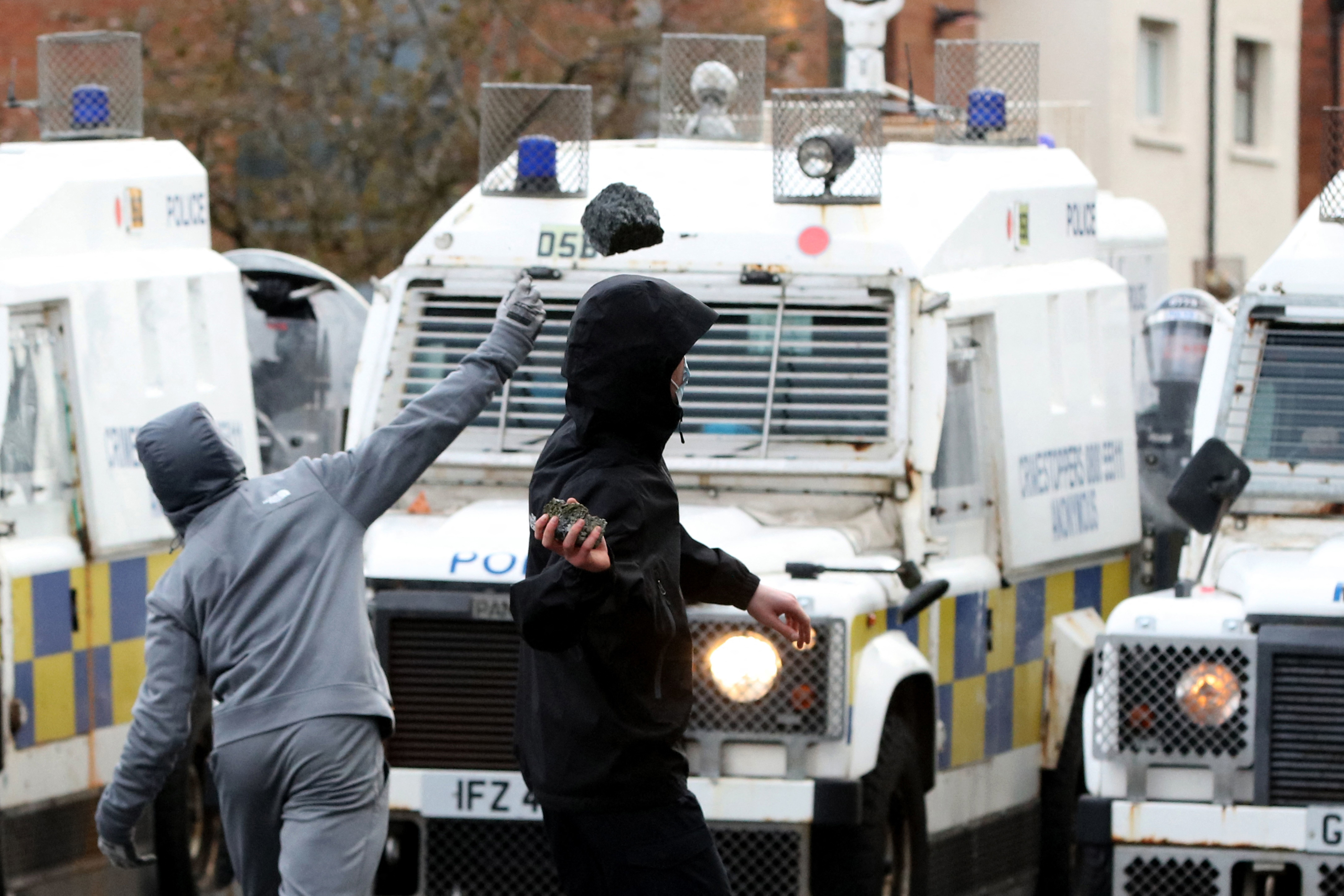 Two people stand in front of a row of security vehicles in Belfast, Northern Ireland. One is throwing an object at the police vehicles.