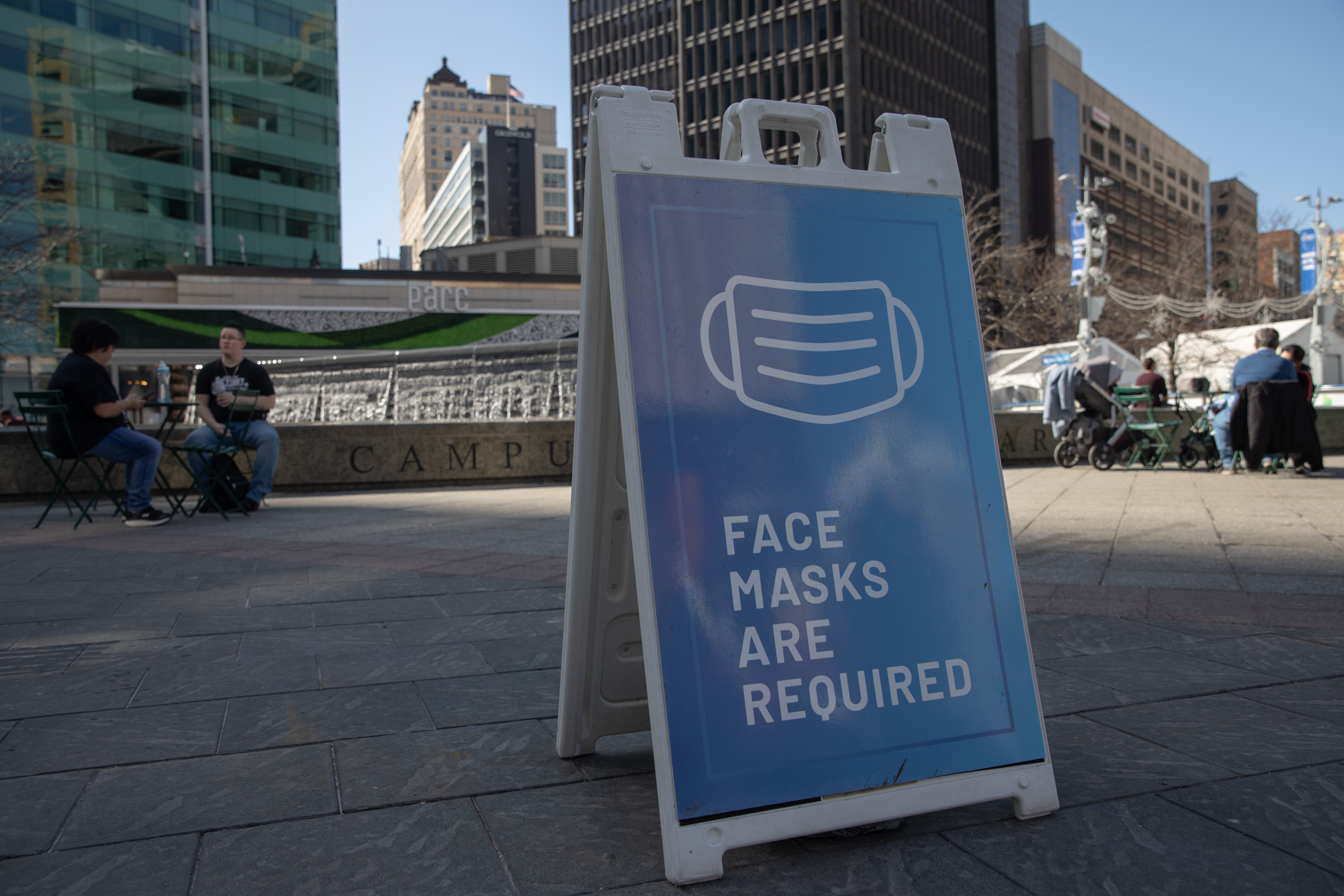 "A sidewalk sign in Michigan reads, ""Face masks are required."""