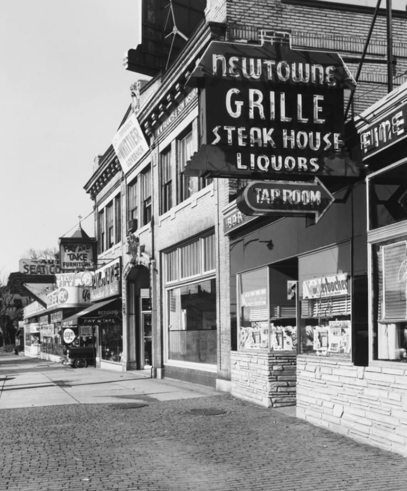 """A black and white photo of Newtowne Grille in Porter square, taken in the 1960s. The sign reads, """"Newtowne Grille: Steakhouse, Liquors, Tap Room."""""""