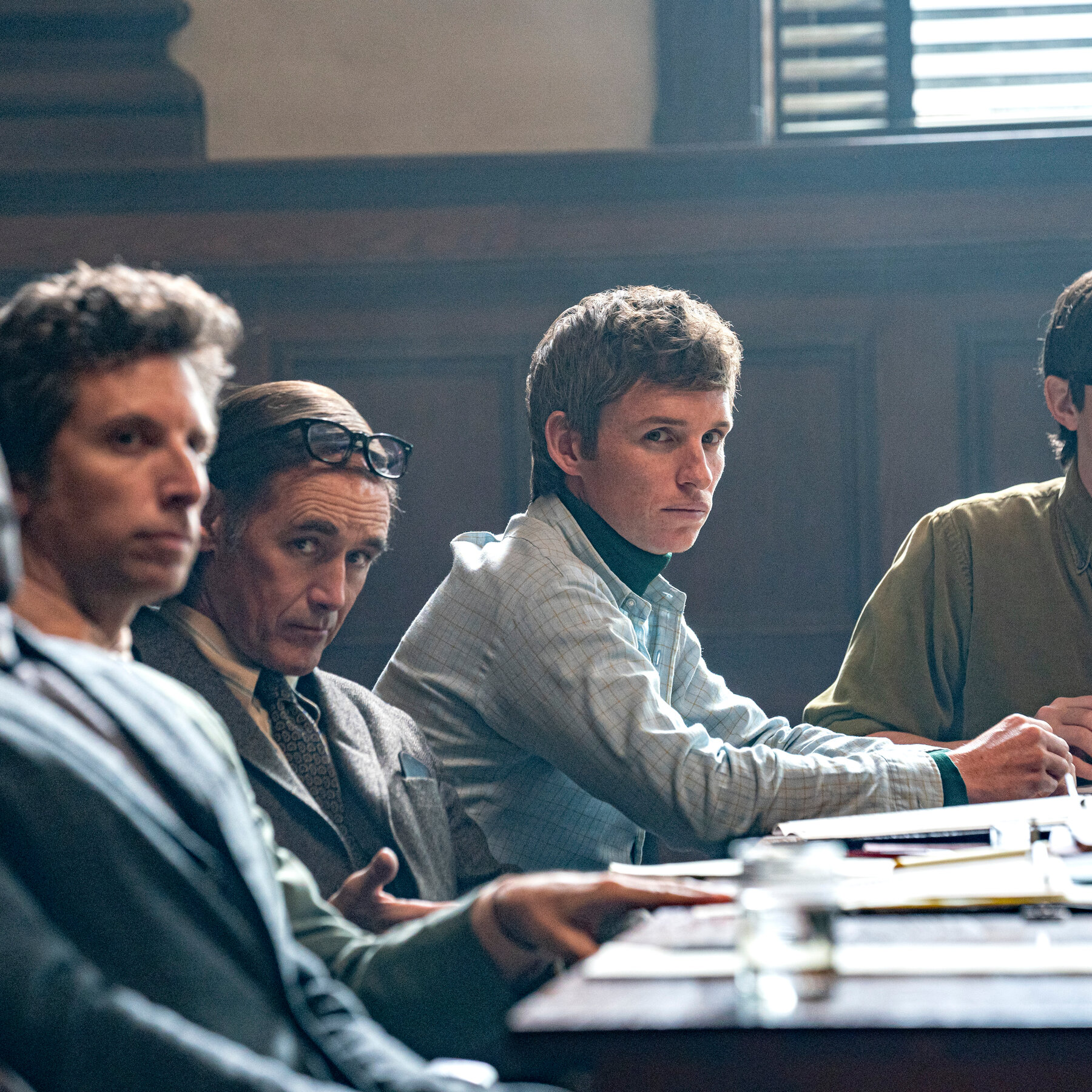 Several white men sit at a courtroom table.