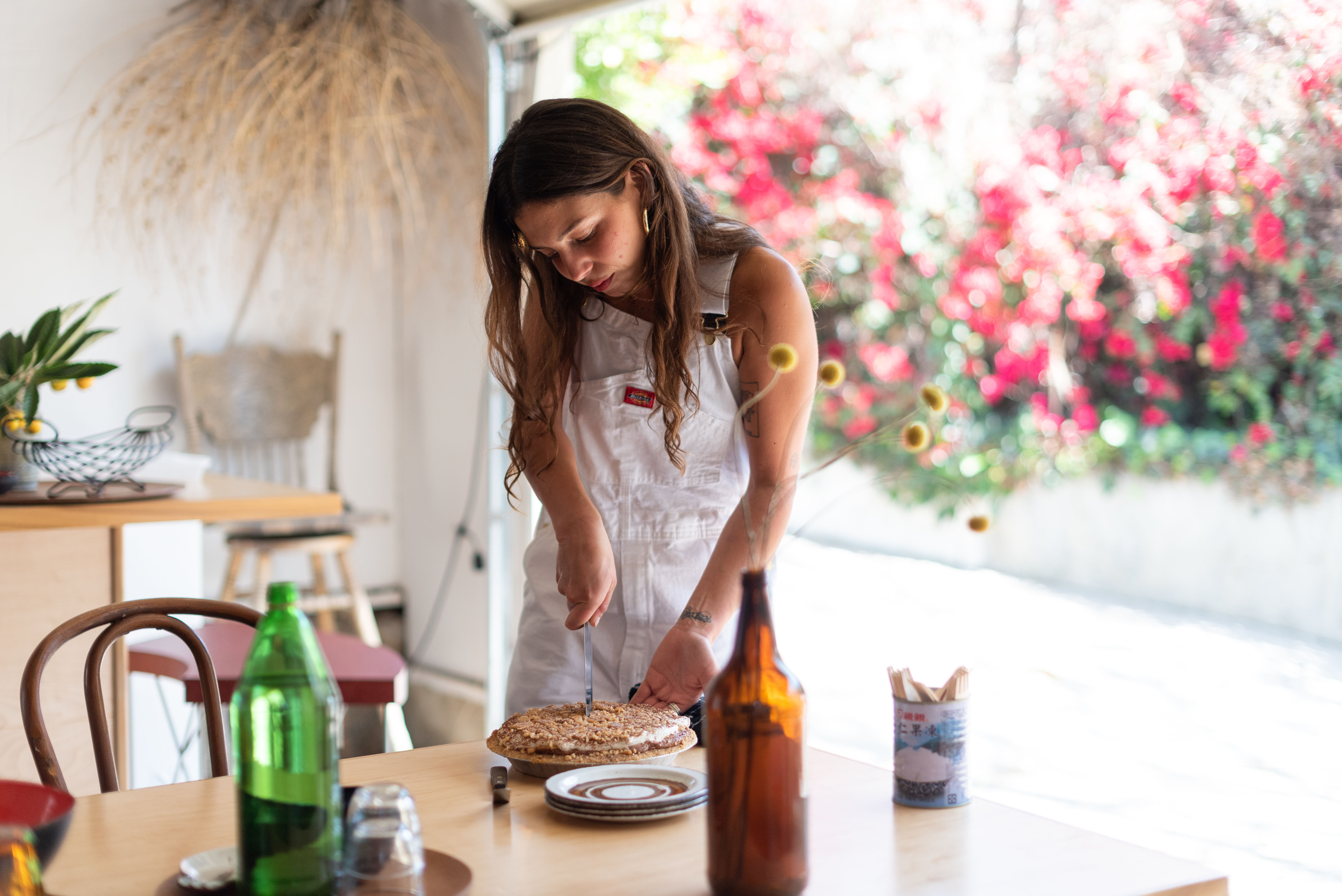Woman wearing while overalls cuts into a pie standing near a garage door that leads to the outside.