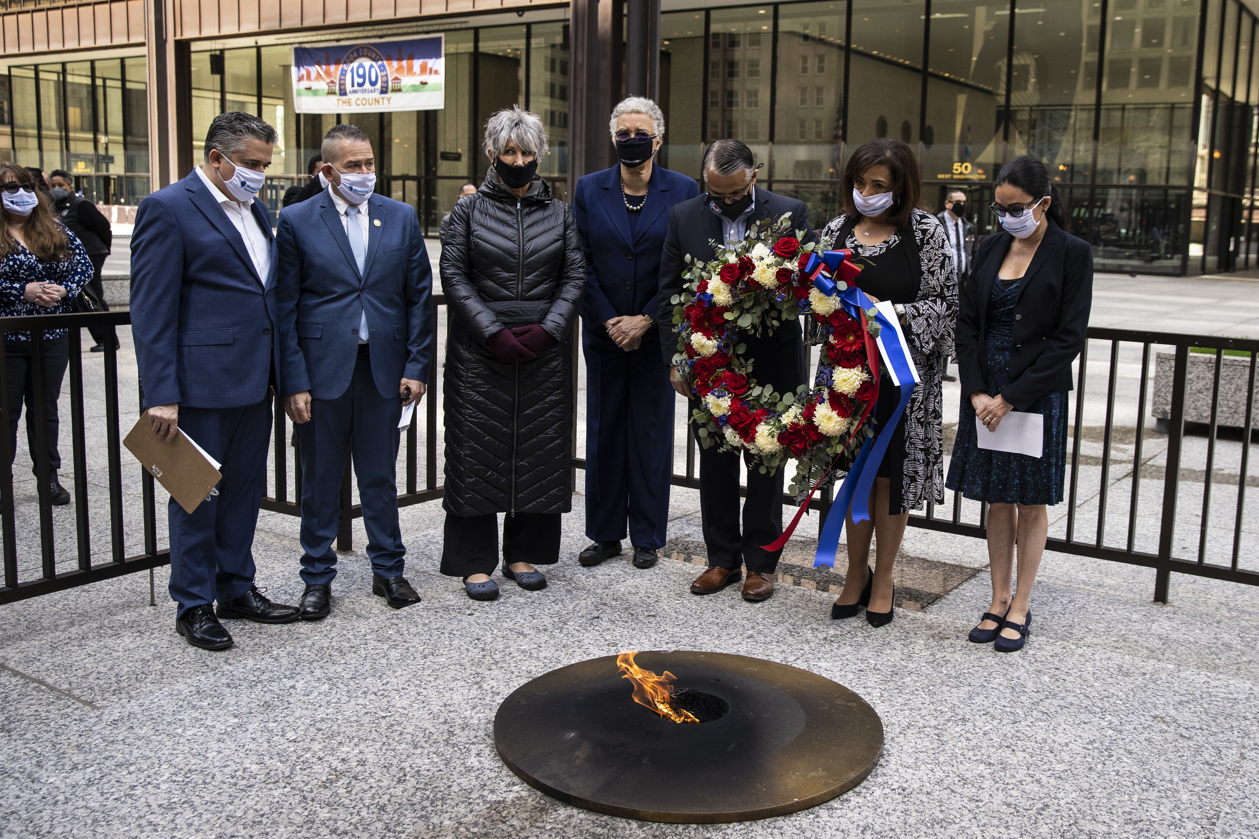 (From left) Xavier Nogueras and Cesar Rolon, of Illinois Unidos, Cook County Treasurer Maria Pappas, Cook County Board President Toni Preckwinkle, Ald. Gilbert Villegas (36th), Cook County Clerk of the Circuit Court Iris Martinez and Dr. Marina Del Rios, from University of Illinois Hospital & Health Sciences System, lay a wreath near the Eternal Flame Memorial at Daley Plaza in honor of essential workers and the Brown and Black communities hit hard by COVID-19, Monday, April 12, 2021.