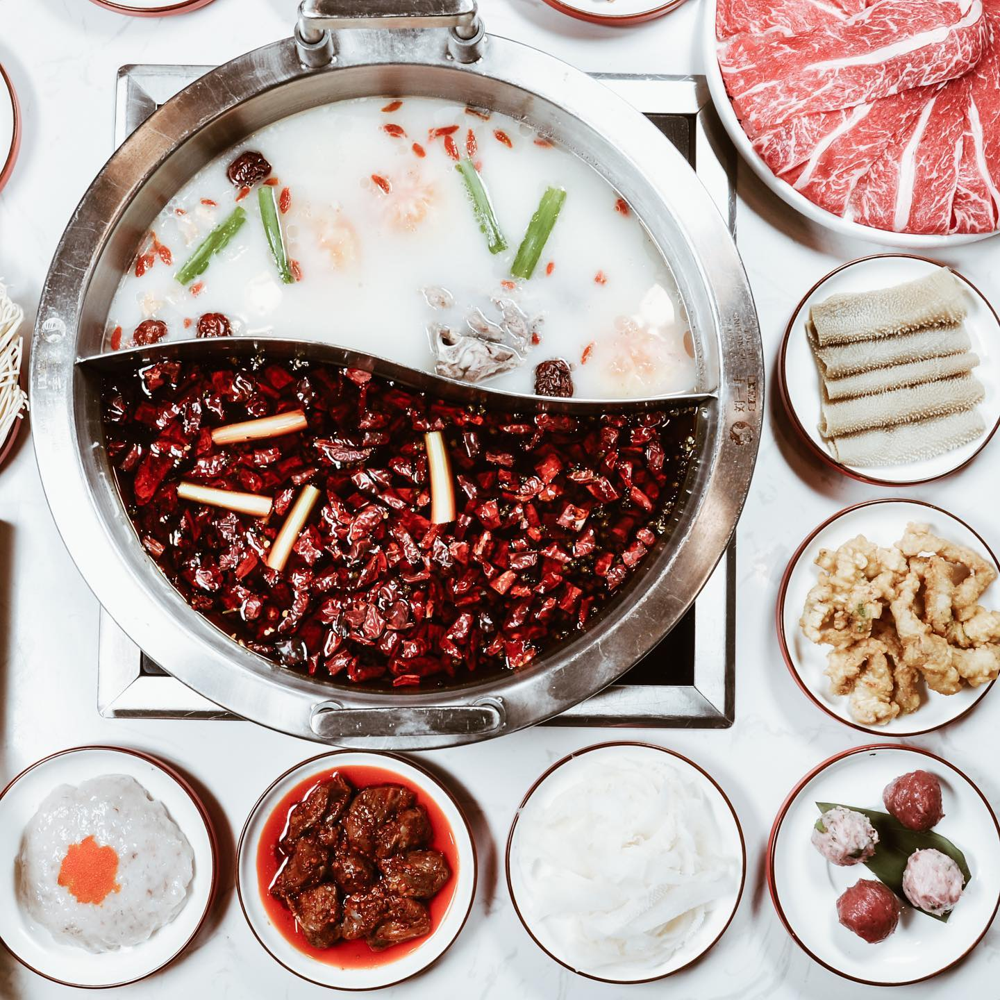 A half-and-half hot pot garnished with chiles, green onions. A selection of dishes sits on the side.
