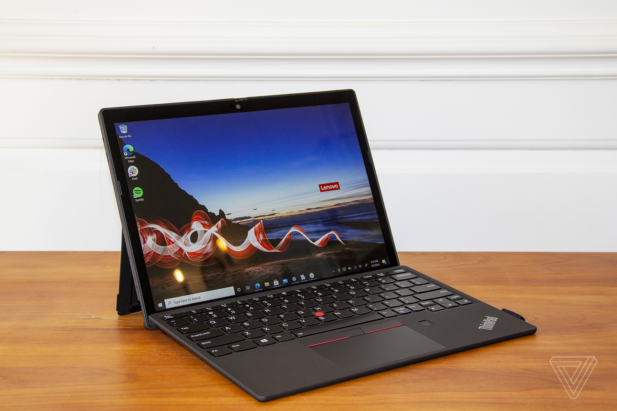 The ThinkPad X12 Detachable open from the front, angled to the right. The screen displays a beach with a red ribbon across it and the Lenovo logo on the horizon.