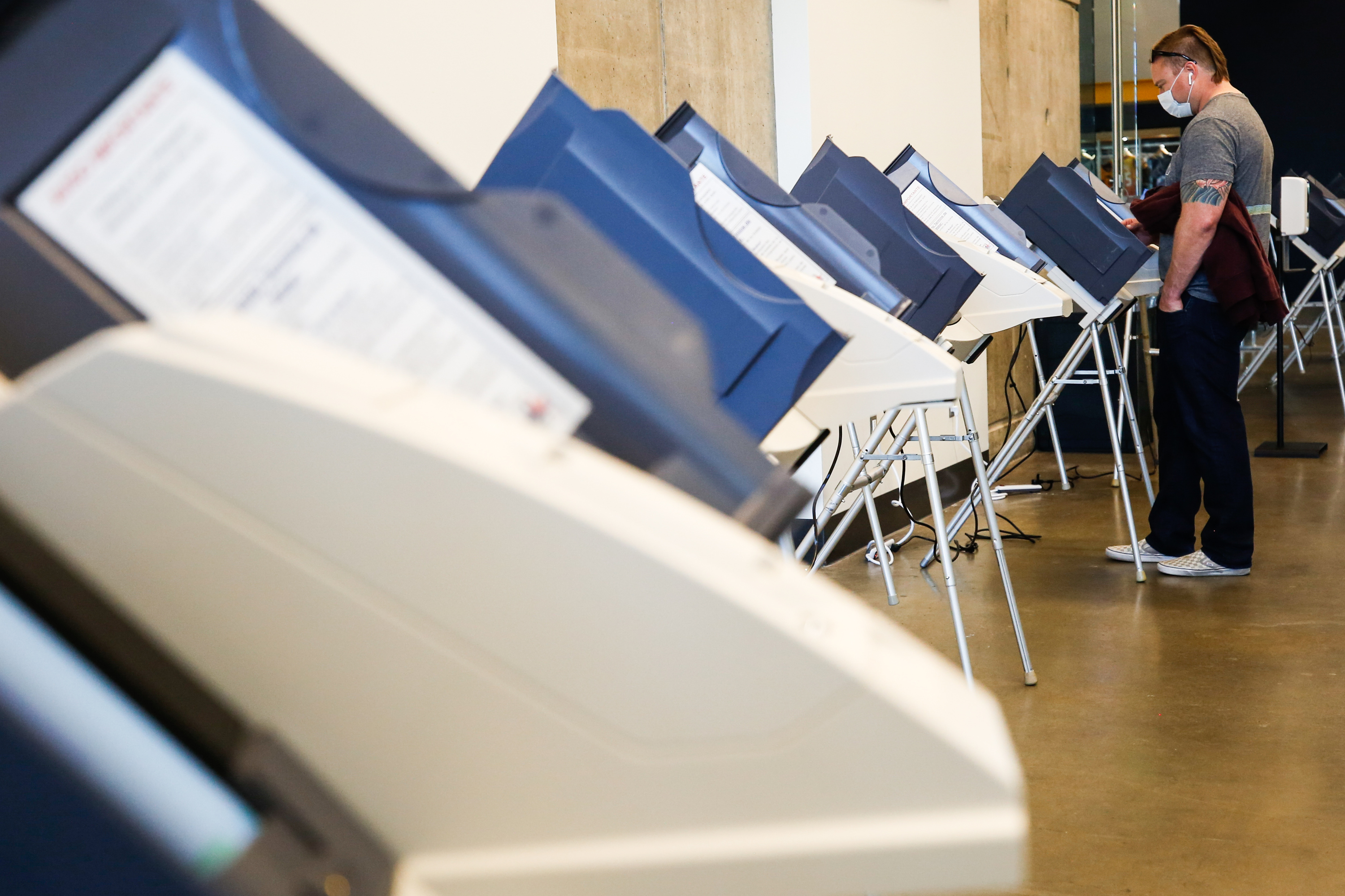 A voter fills in the ballot on the voting machine during the Election Day voting at Vivint SmartHome Arena.