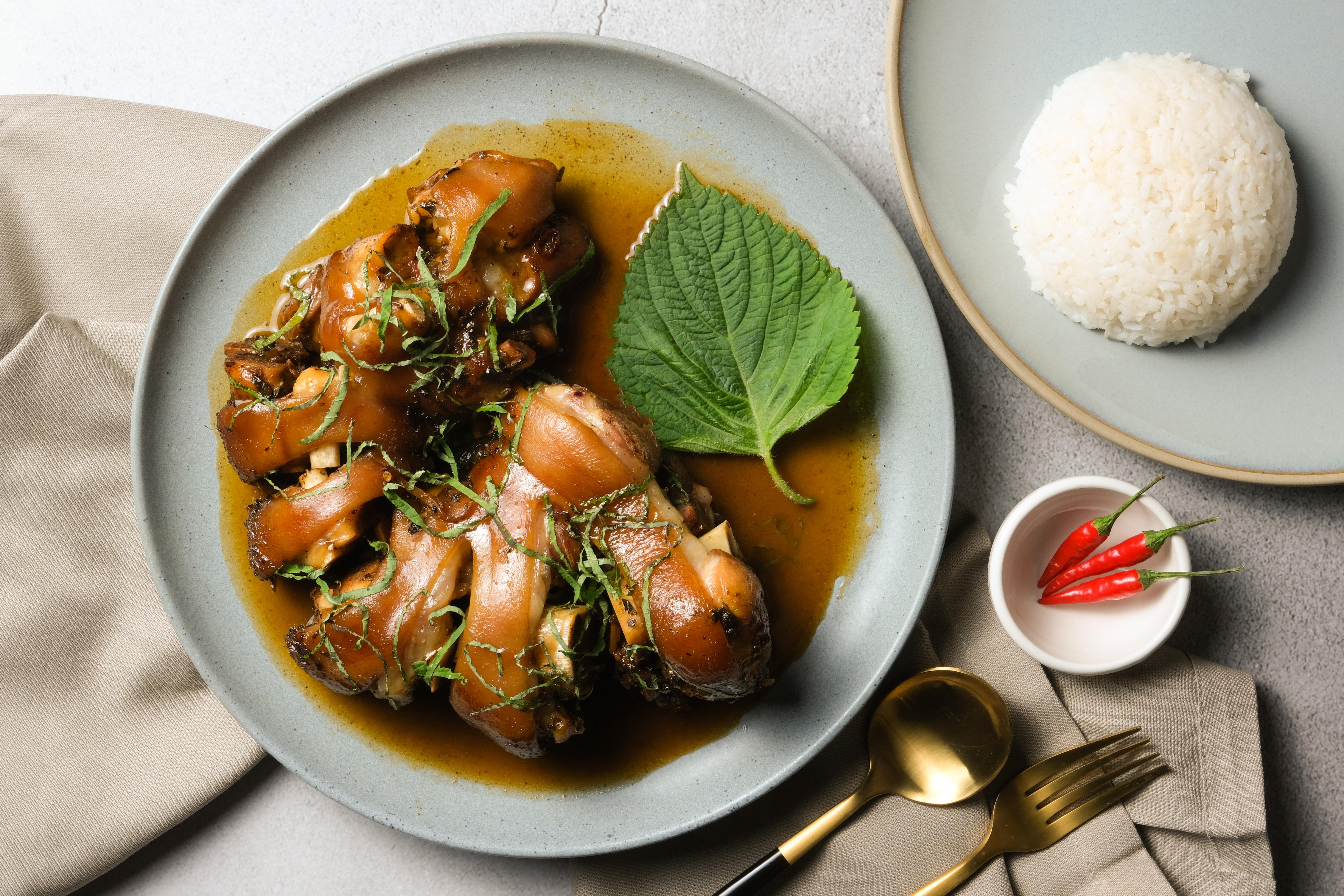 一盘是红烧猪蹄,旁边放着一小碗红辣椒,另一盘上面放着一堆白米饭;还有一把叉子和一把勺子,还有一张米色的餐巾,放在盛猪蹄的盘子下面。