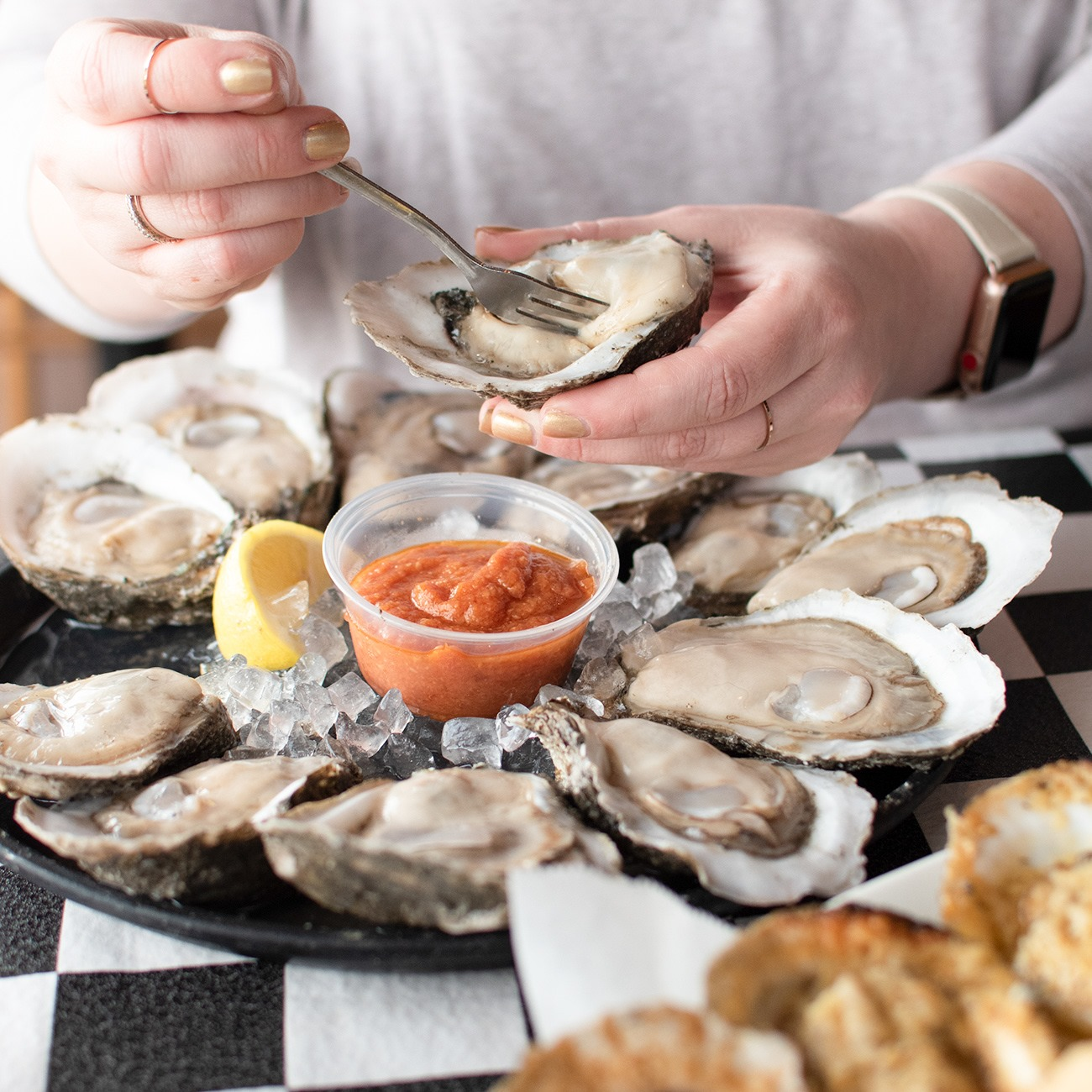a person eating raw oysters from the halfshell with a fork