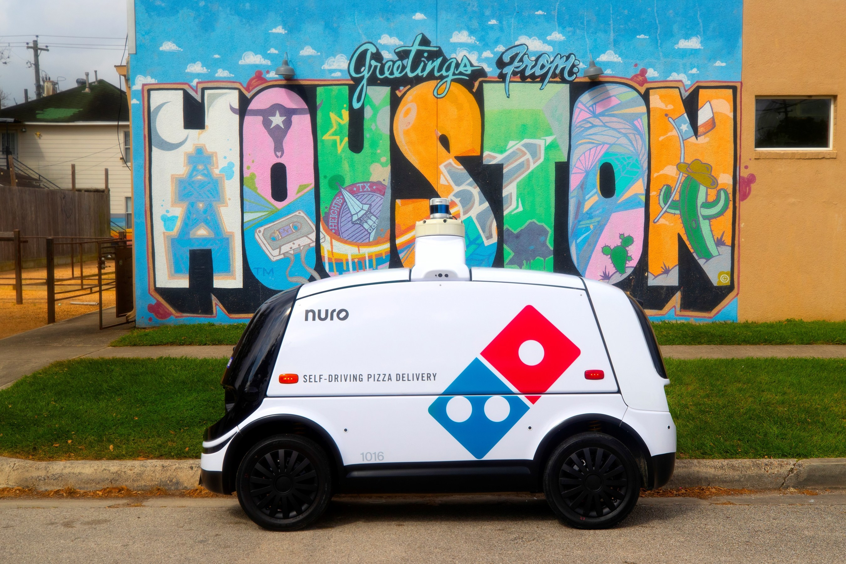 A van-resembling autonomous vehicle with a Domino's logo painted on its side, in front of a Houston mural.