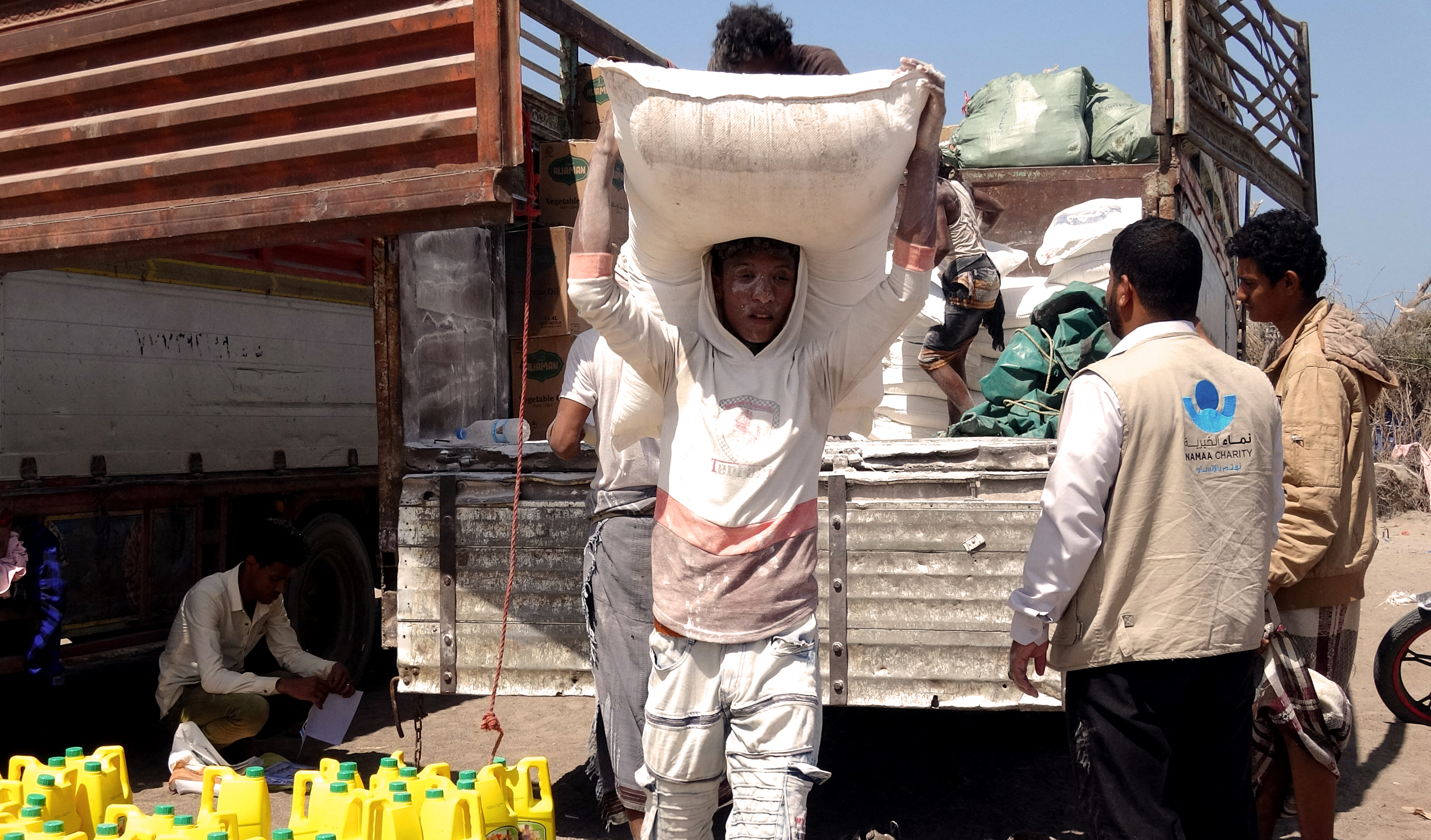 A person carrying a large sack of food, taken from the back of a small truck, on their head.