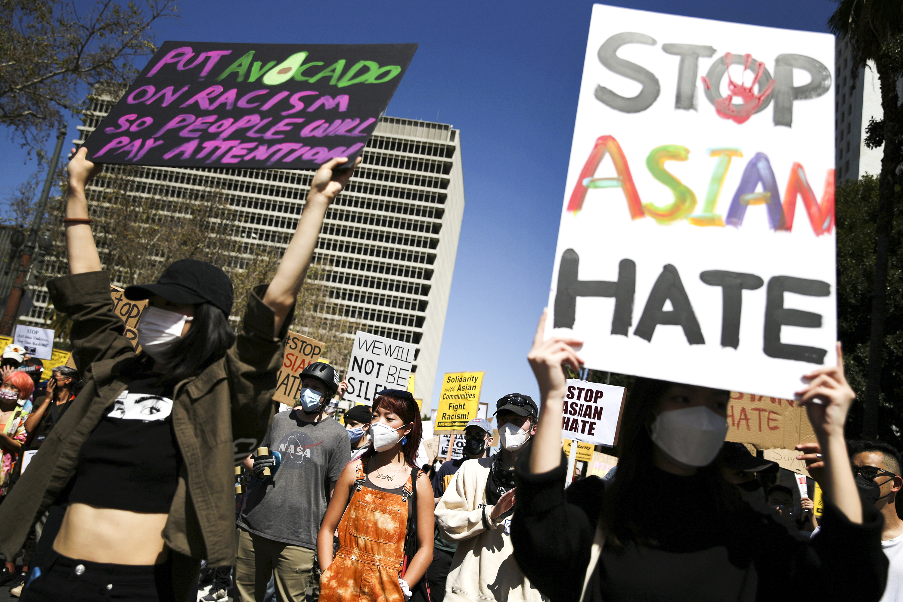"Protesters march down a city street and carry signs, one that reads, ""Stop Asian hate,"" and the other, ""Put avocado on racism so people will pay attention."""