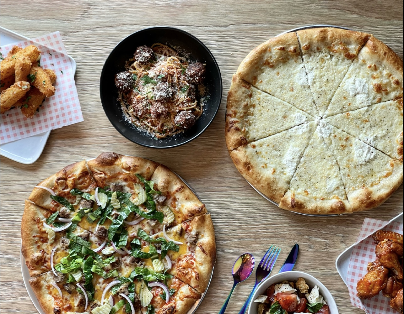 Wings, pizza with greens, meatballs, and a sliced cheese pizza on a wooden table