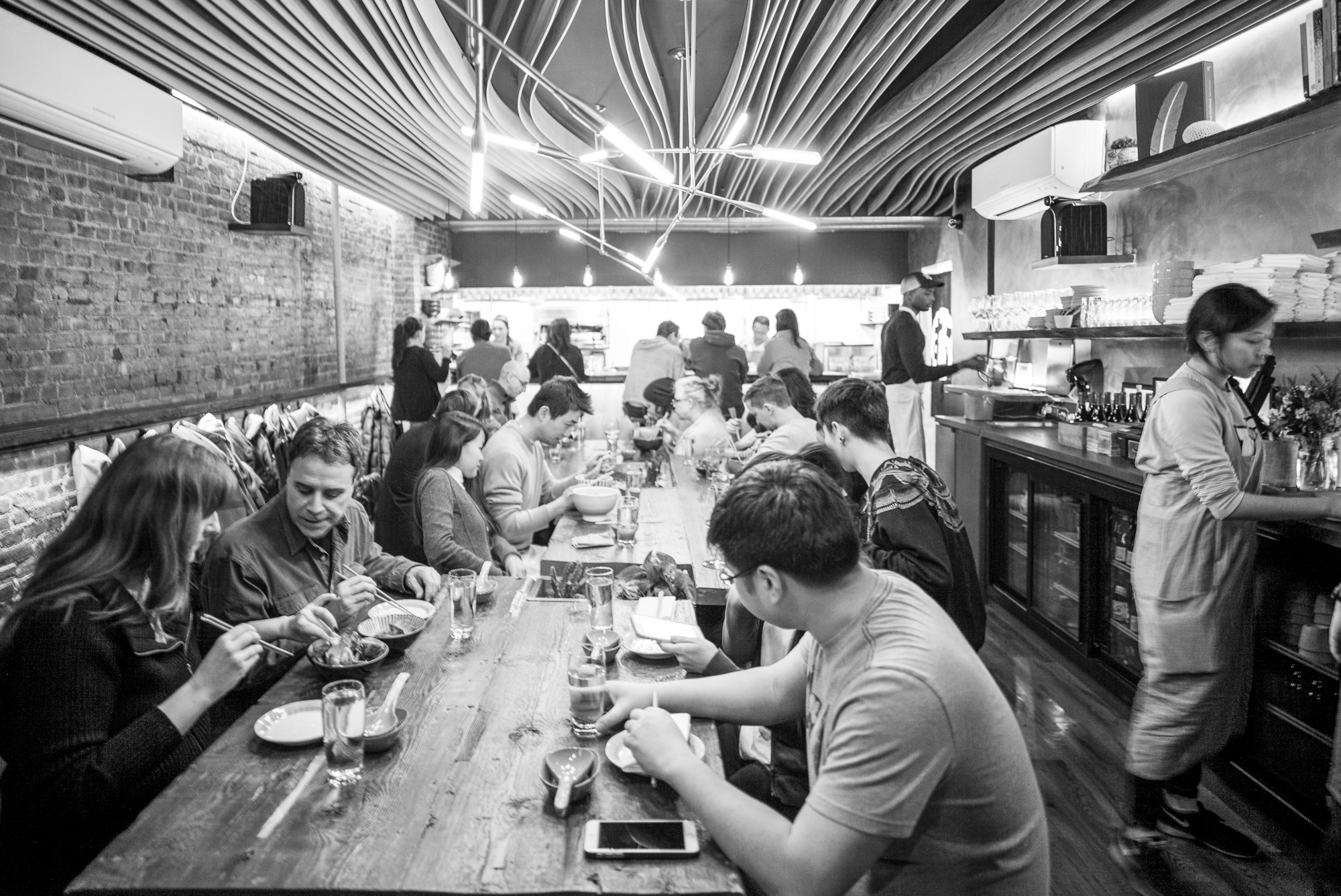 Diners slouch over bowls of steaming ramen at a lengthy wooden table in a restaurant