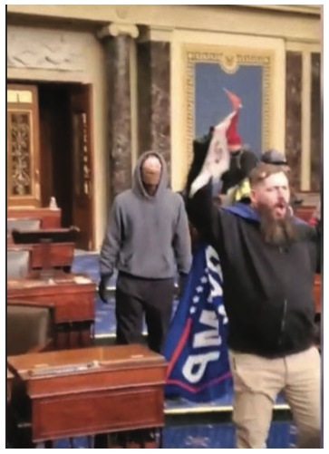 Federal authorities say this photo depicts Thomas B. Adams Jr. holding a Trump flag on the floor of the U.S. Senate on Jan. 6, 2021.