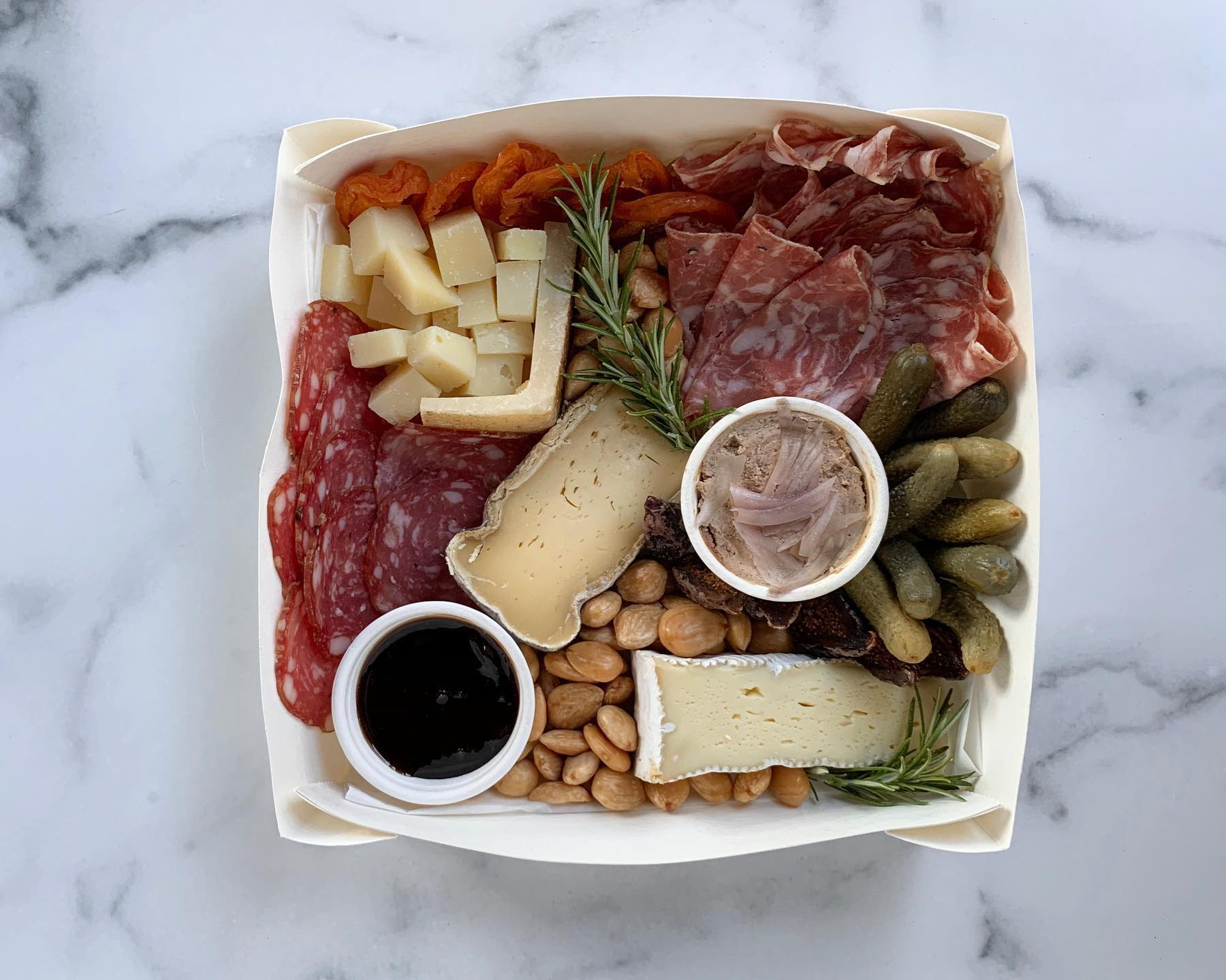 Meat, cheese, pickles, and tinned fish in a takeout box