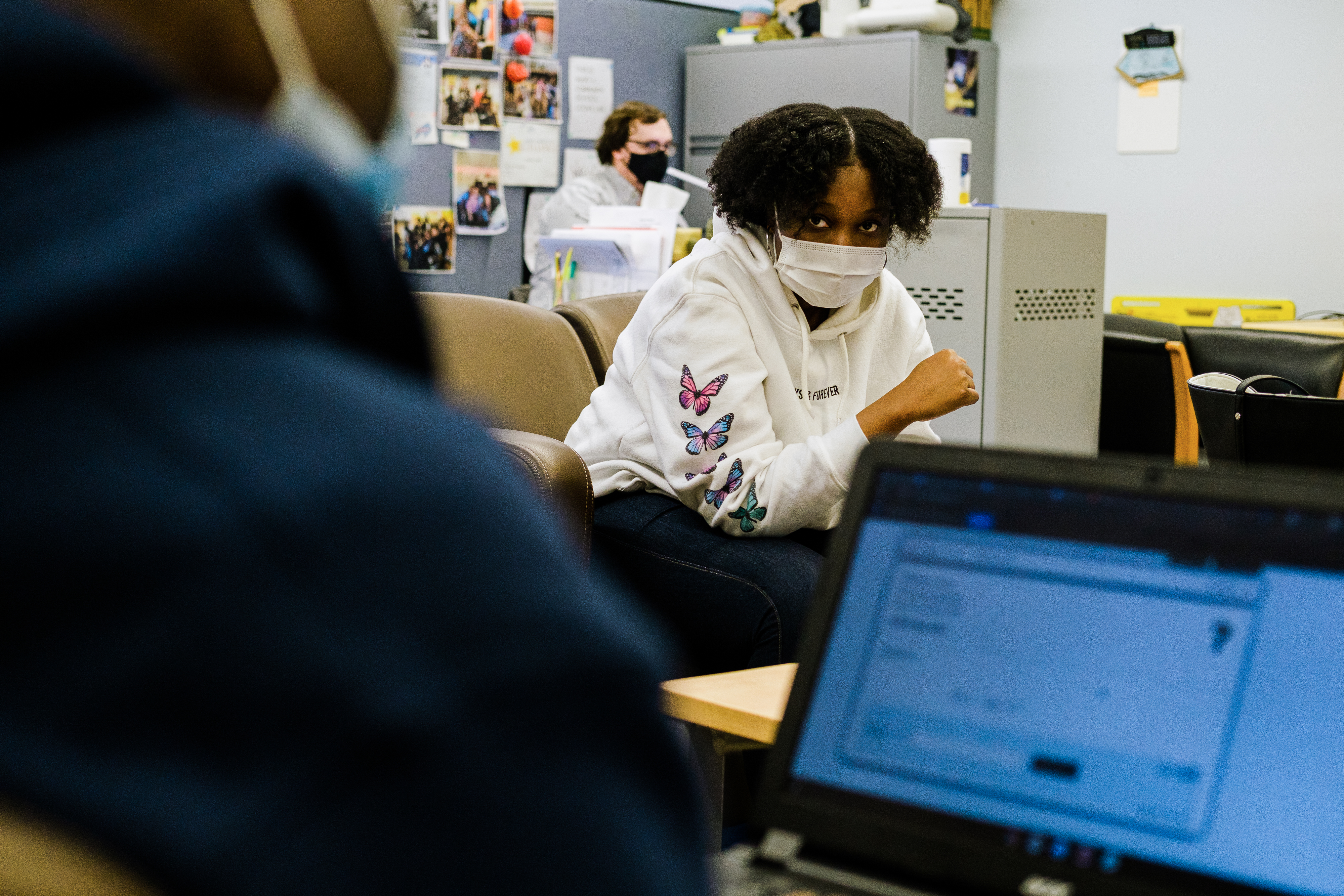 A young woman wearing a protective mask, white hoodie with blue and pink butterflies sits across from a young man wearing a blue hoodie working on a laptop. There is a male teacher sitting behind a desk in the background.