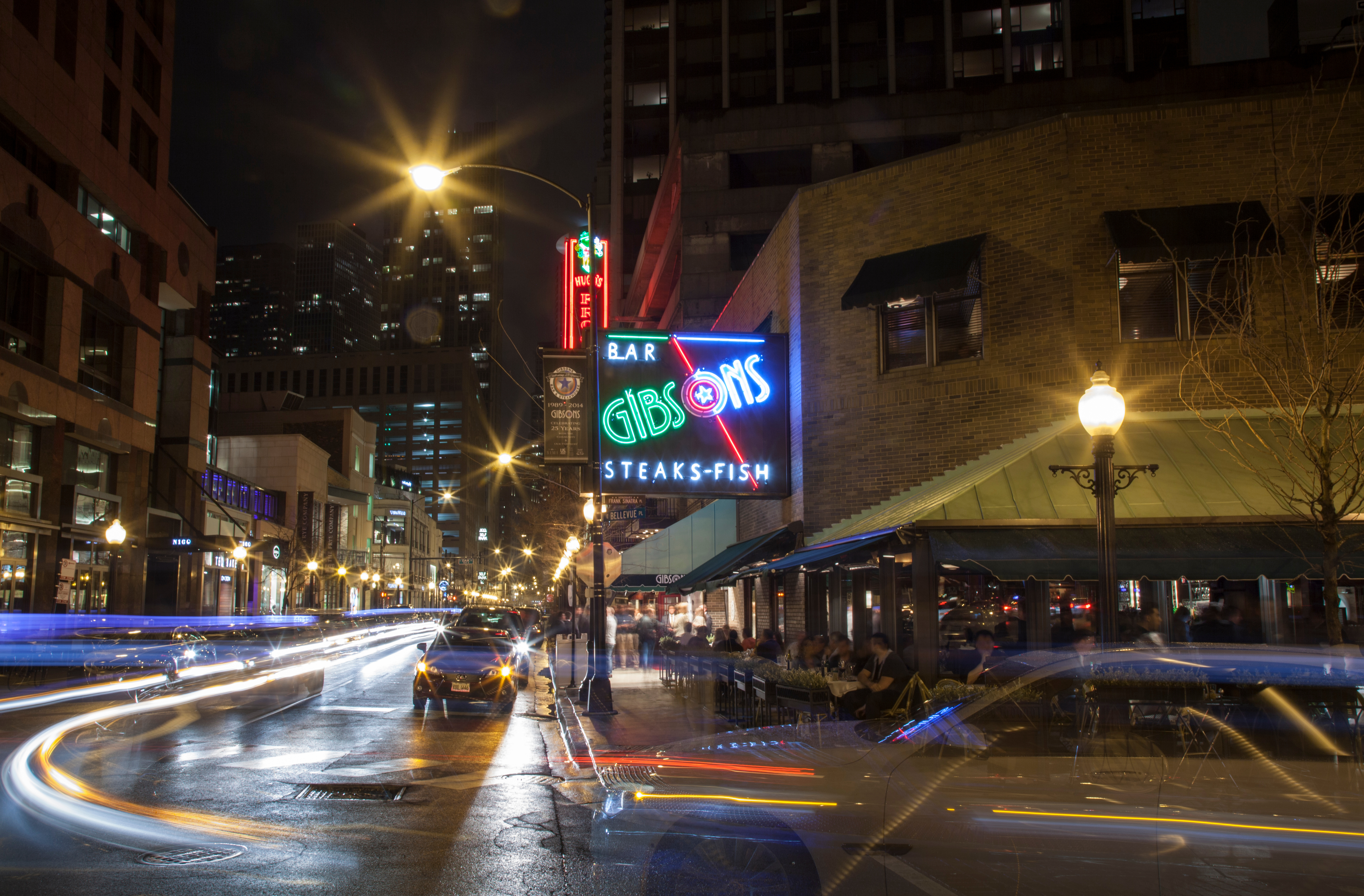 A neon restaurant sign with motion photography showing blurred cars at night.